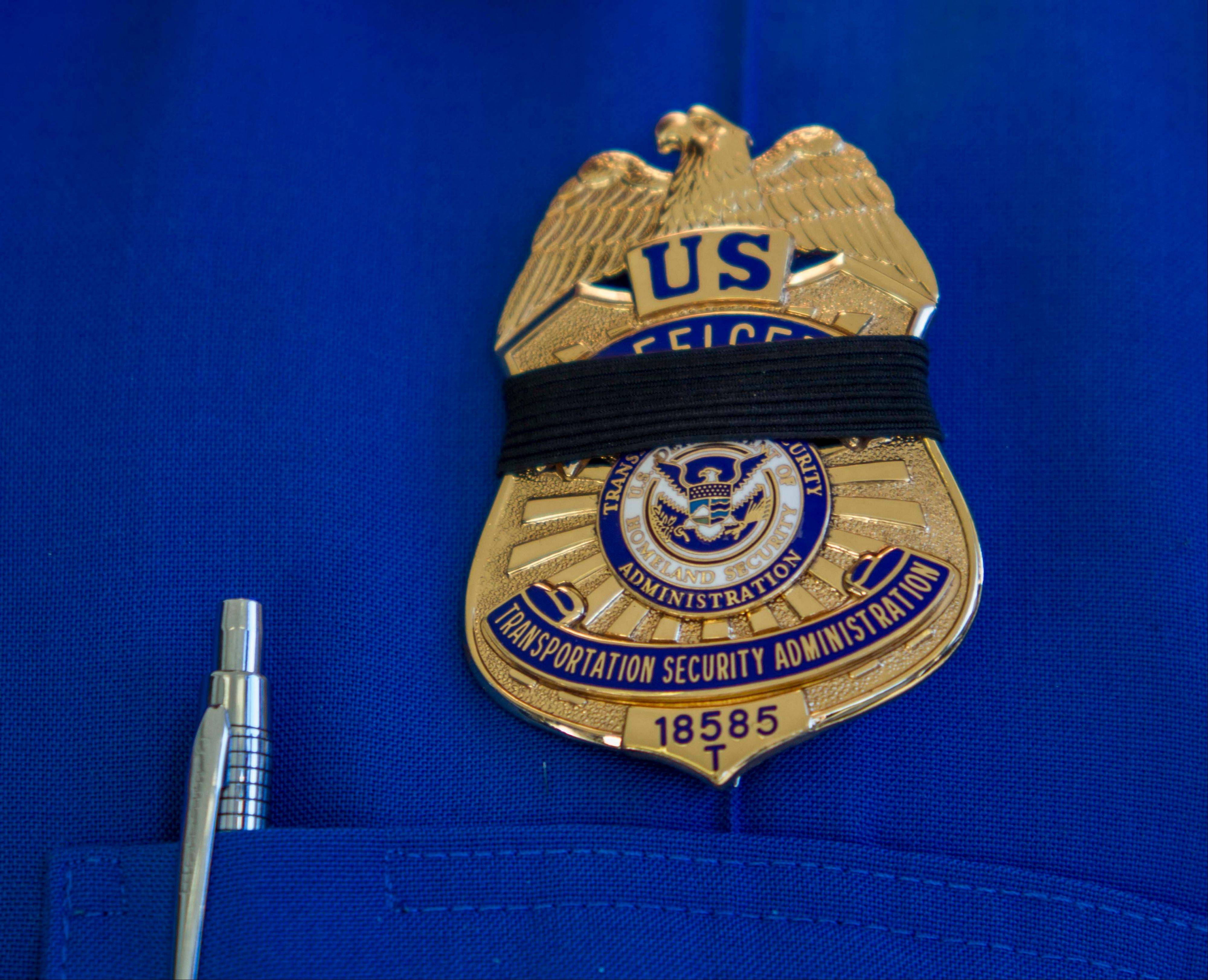 A Transportation Security Administration employee wears a black ribbon Saturday over his badge,in Los Angeles International Airport.