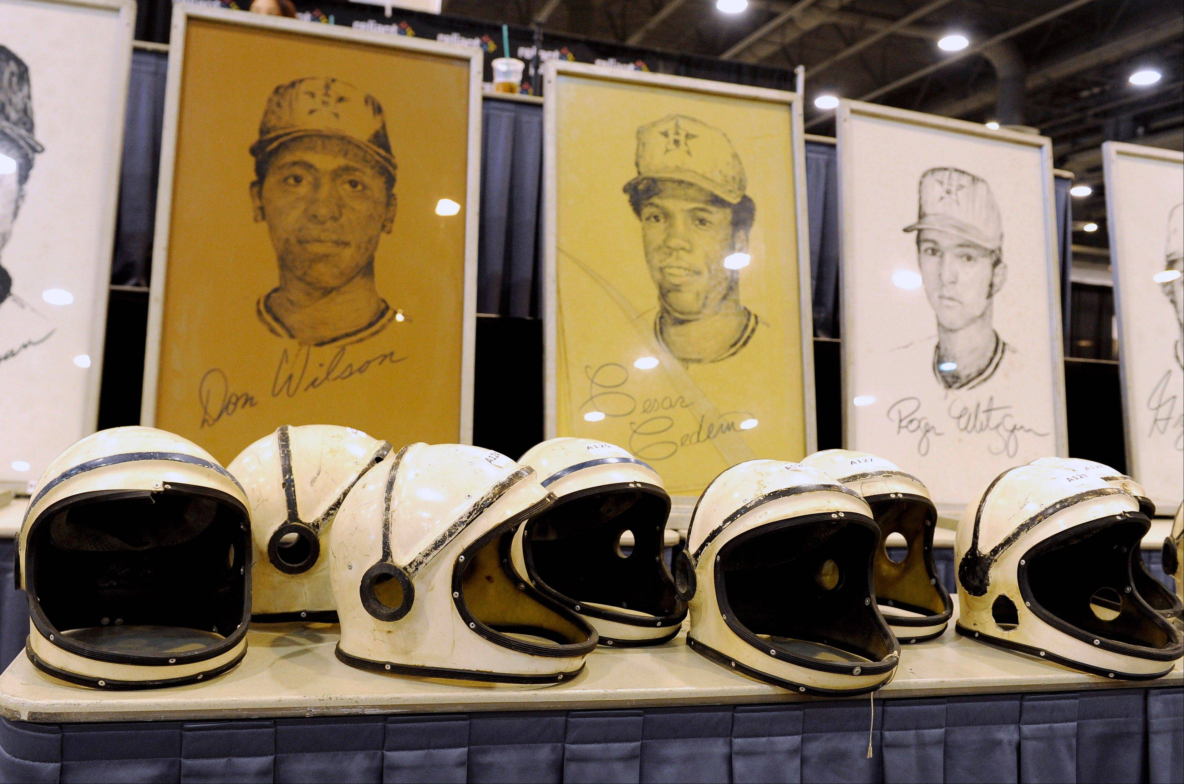 Space helmets worn by the grounds crew in the early years of the Houston Astrodome are lined up Saturday in front of drawings of former Houston Astros players at the Reliant Center in Houston. A sale and auction of Houston Astrodome furniture, appliances, Astroturf and staff uniforms was held Saturday. The Astrodome was the world's first multipurpose domed stadium and was once home to the Astros and the Oilers.