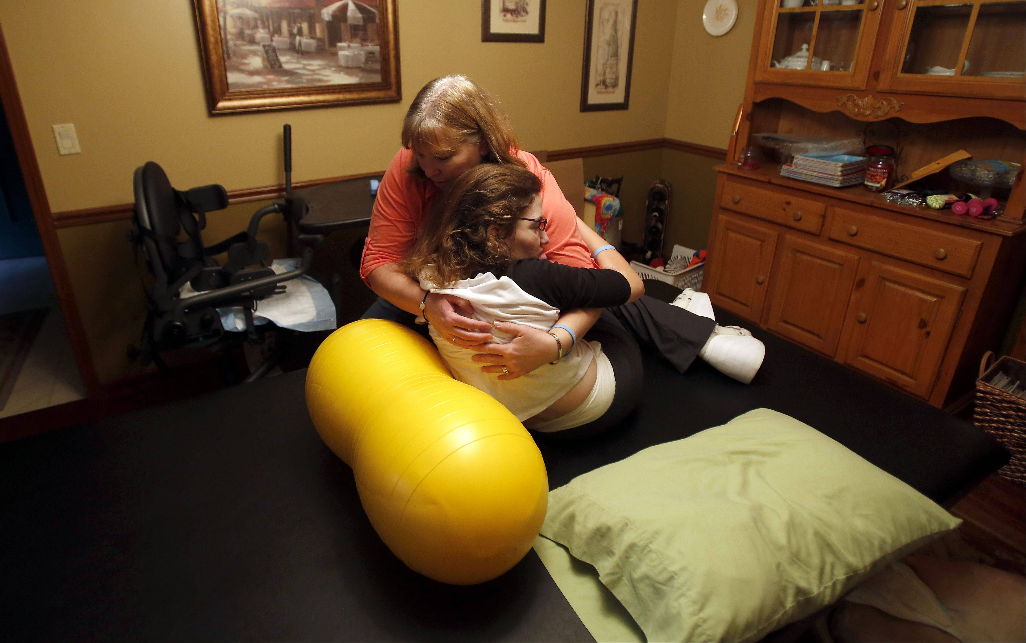 Alex Frerichs, 24, of Elgin gets some help from mom Annette as she does physical therapy in the family's dining room.