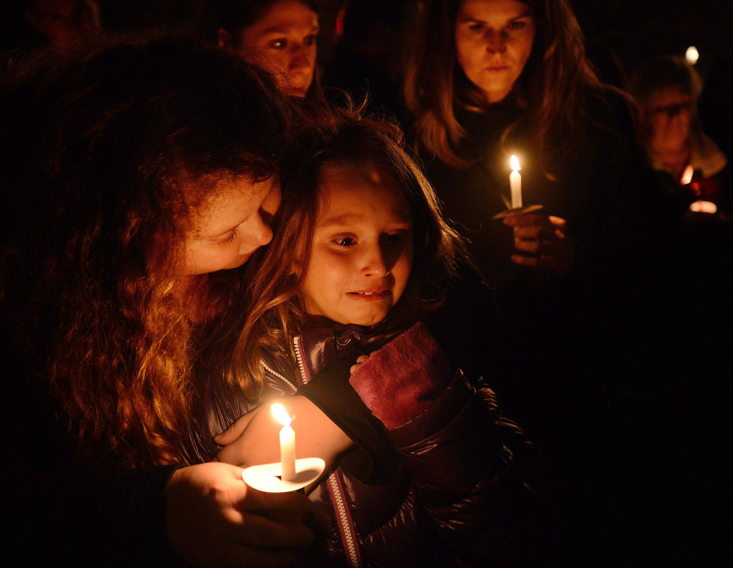 Teresa Russo, left, the daughter of Frank Russo, consoles Kaylee Roden, his grandniece, during Friday's candlelight vigil.