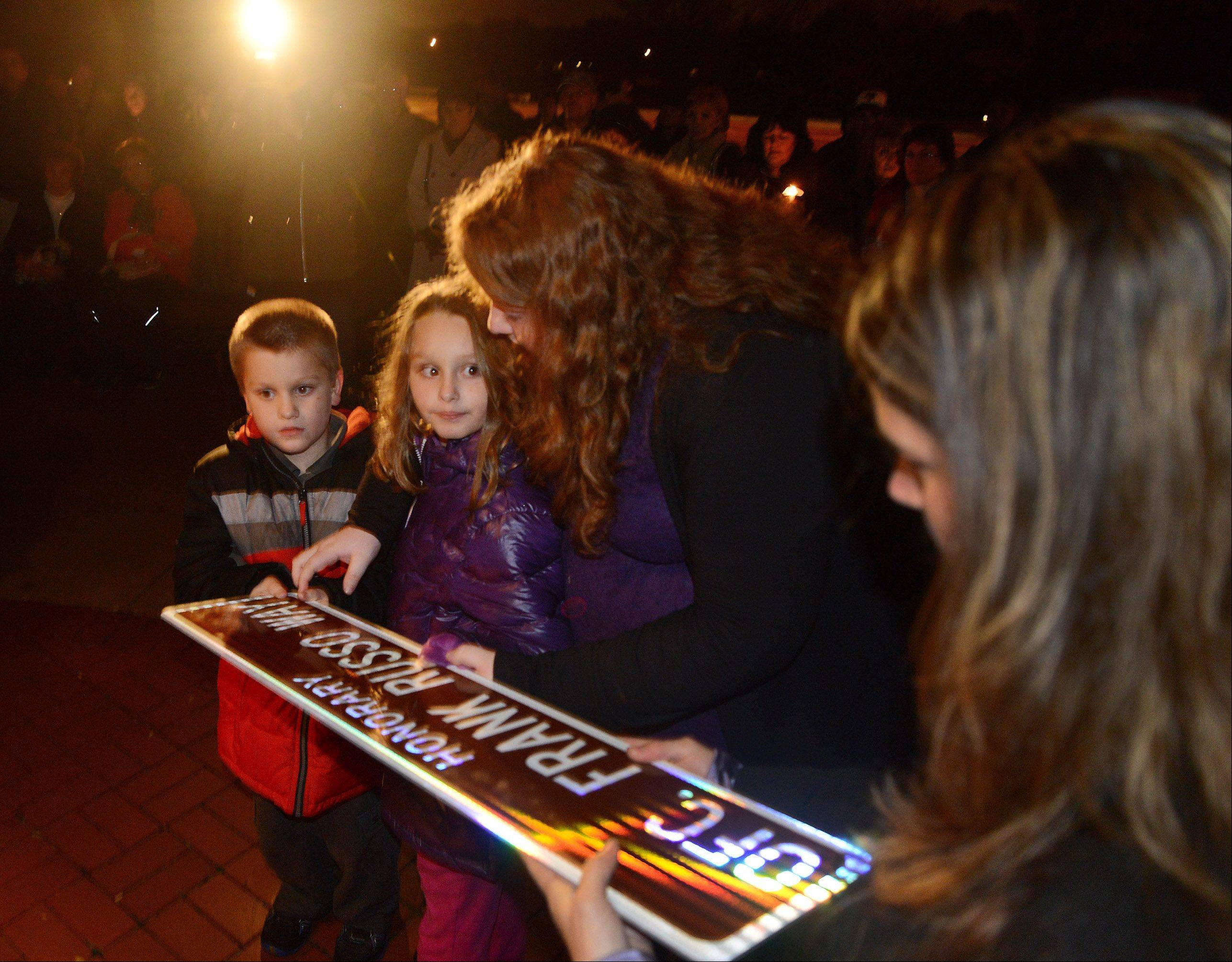From left, family members Jimmy Roden, Kaylee Roden, Teresa Russo and Jenny Russo are presented an honorary street sign Friday night during a special ceremony to rename Hammond Drive as Officer Frank Russo Way.