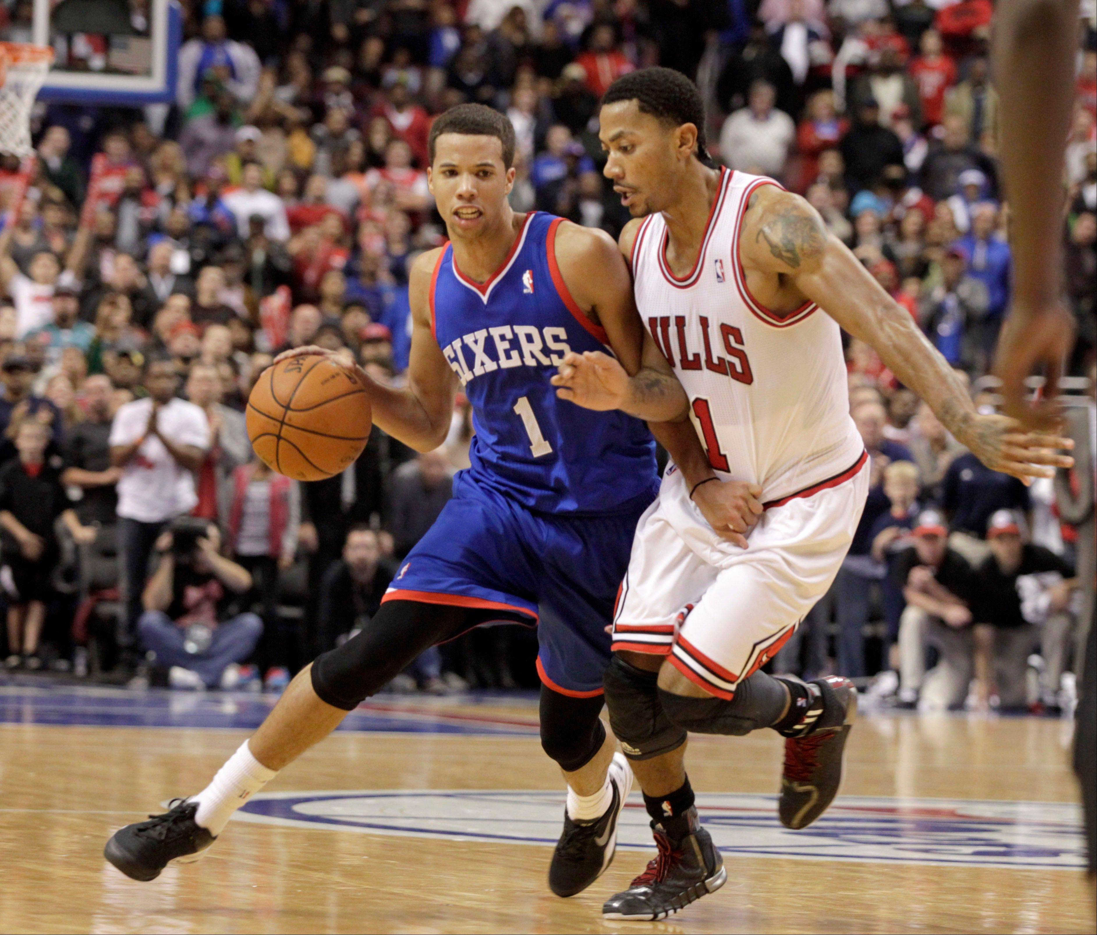 Derrick Rose, right, defends as Philadelphia 76ers' Michael Carter-Williams (1) moves the ball up the court in the second half of an NBA basketball game Saturday Nov. 2, 2013, in Philadelphia. The 76ers won 107-104.