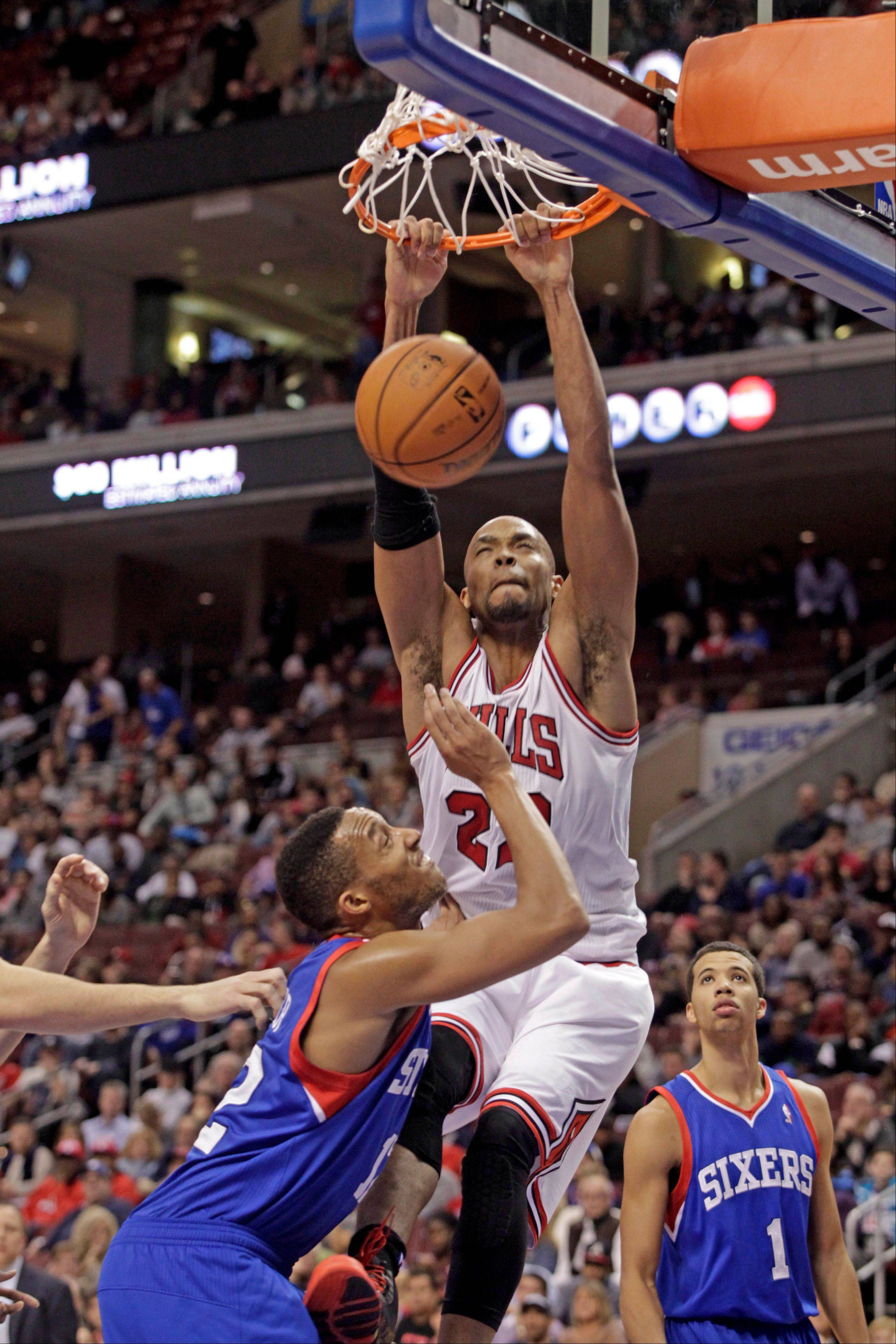 Bulls' Taj Gibson (22) scores over Philadelphia 76ers' Evan Turner in the first half of an NBA basketball game Saturday, Nov. 2, 2013, in Philadelphia.