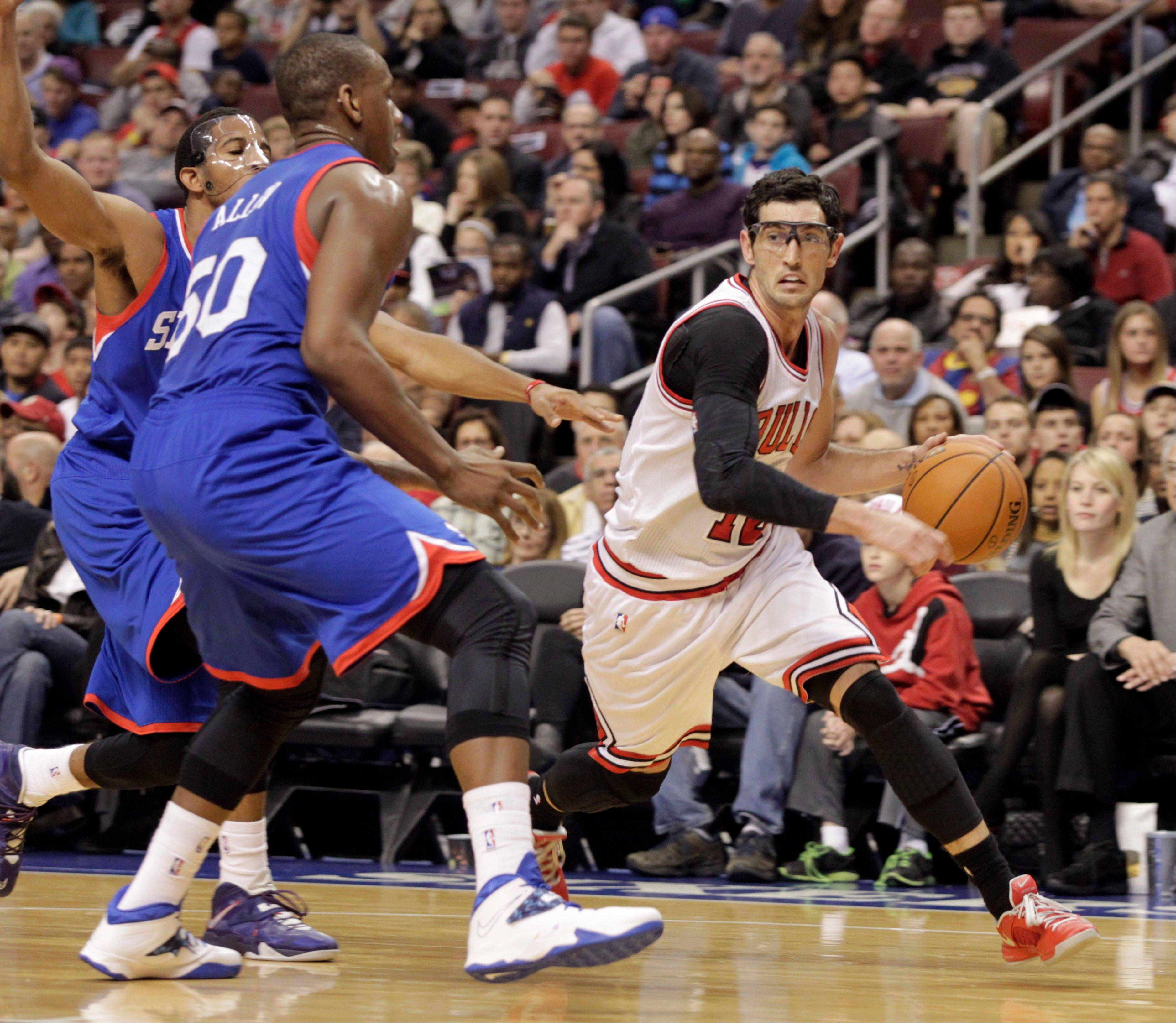 The Chicago Bulls' Kirk Hinrich, right, drives against Philadelphia 76ers' Lavoy Allen (50) in the first half Saturday in Philadelphia.