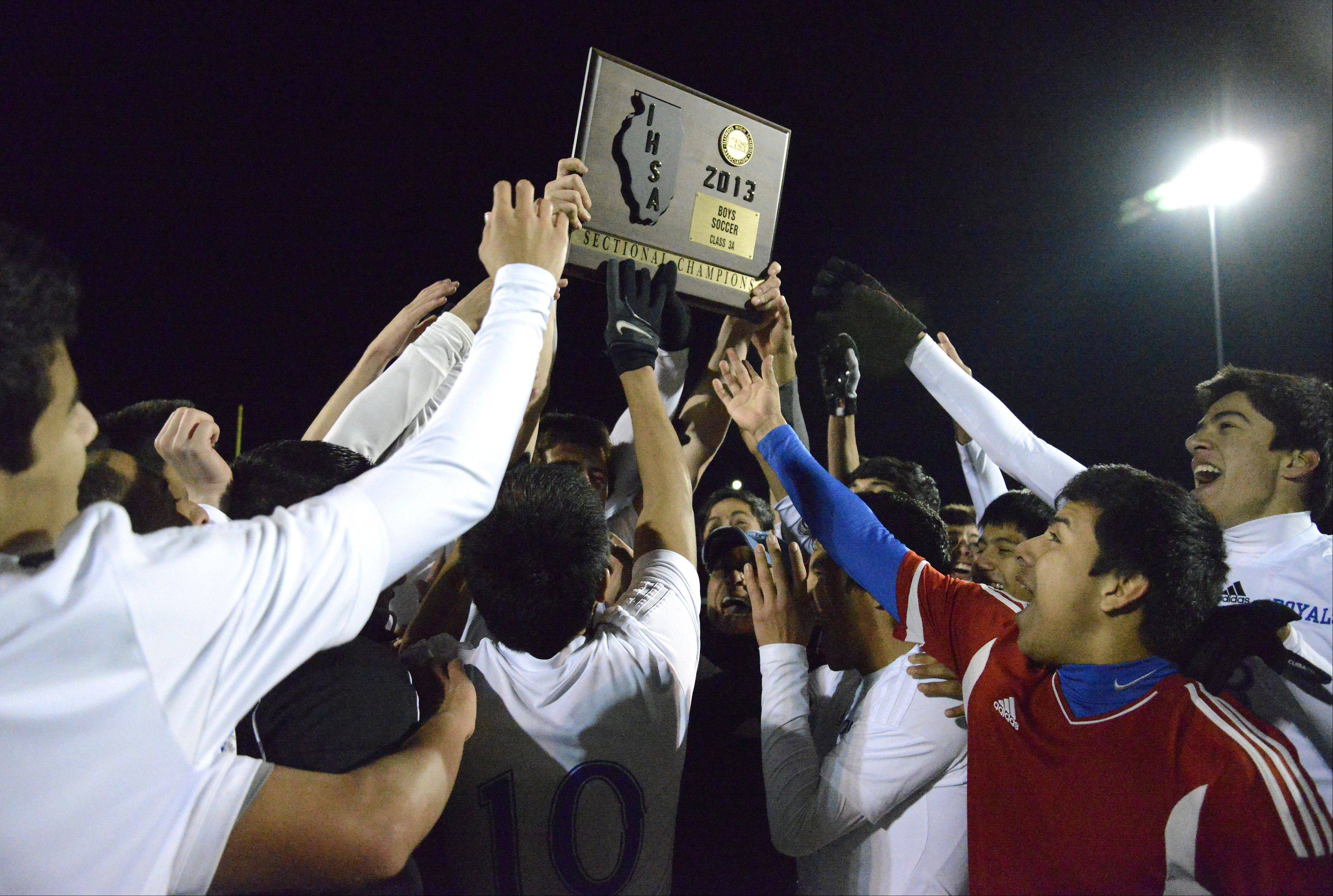 Larkin goalie Aldair Dominguez (right, in red) reaches up to touch the Royals' Class 3A sectional championship plaque after defeating McHenry 1-0 at Huntley High School on Saturday.