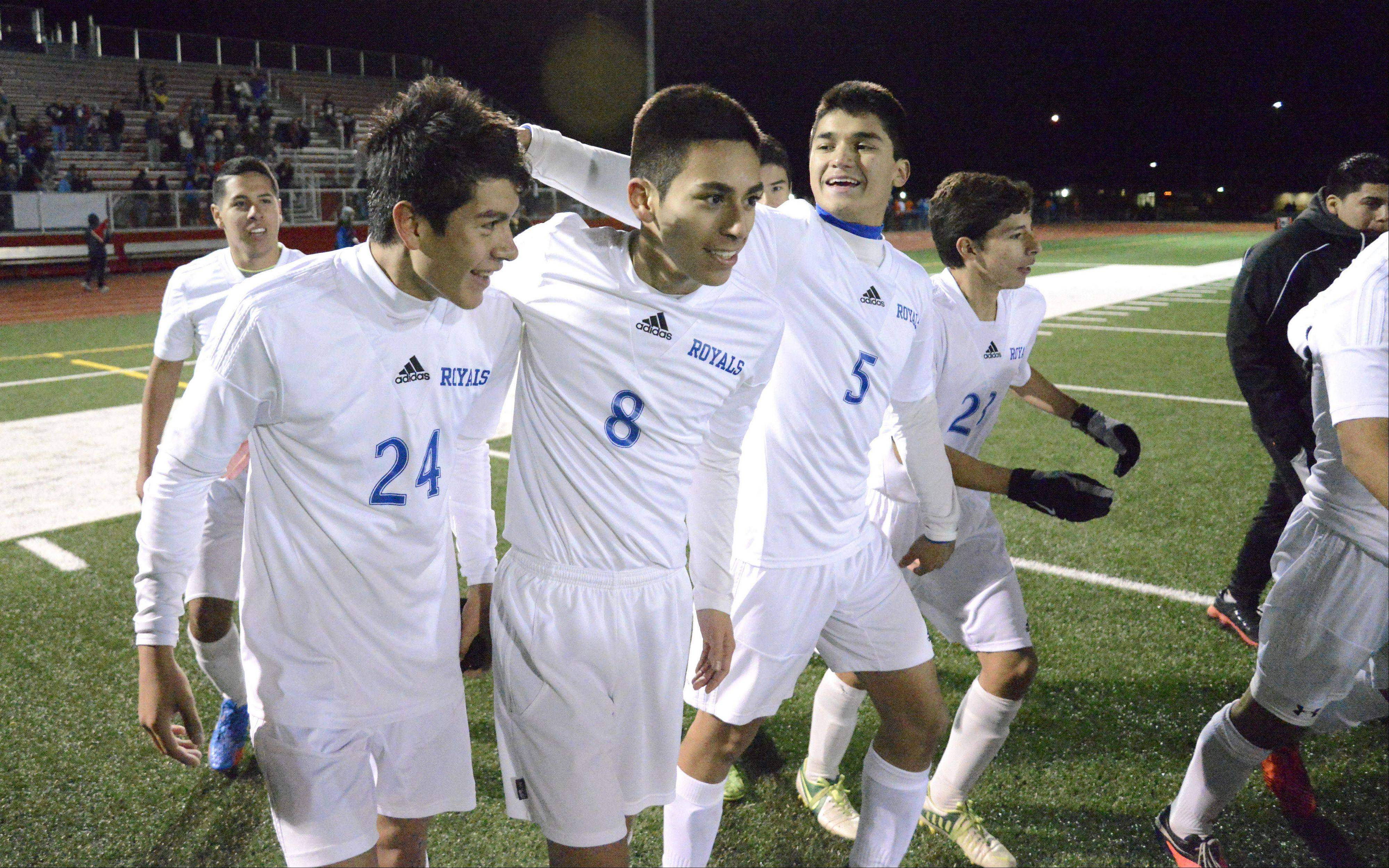 Larkin's Alex Cruz (24) has his hair tousled by teammate Javier Hernandez (5) as they walk with Jesus Avila (8) onto the field to receive their Class 3A sectional championship plaque at Huntley High School on Saturday. Cruz scored the only goal of the game, which gave the Royals the win.