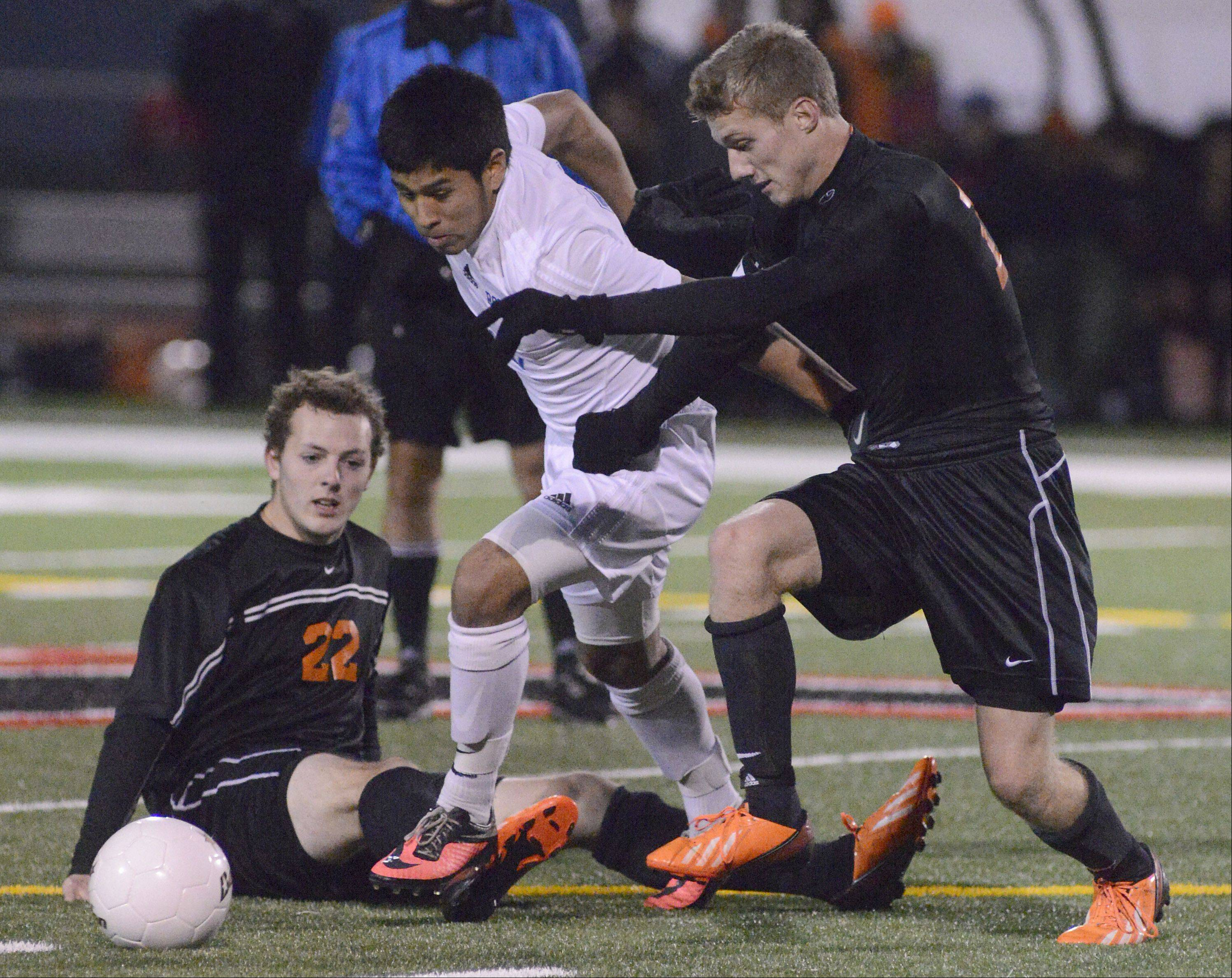 McHenry's Kyle Marsh (22) goes down while teammate Evan Hying continues the fight for the ball with Larkin's Gonsalo Garcia in the second half of the Class 3A sectional championship at Huntley High School on Saturday, November 2.
