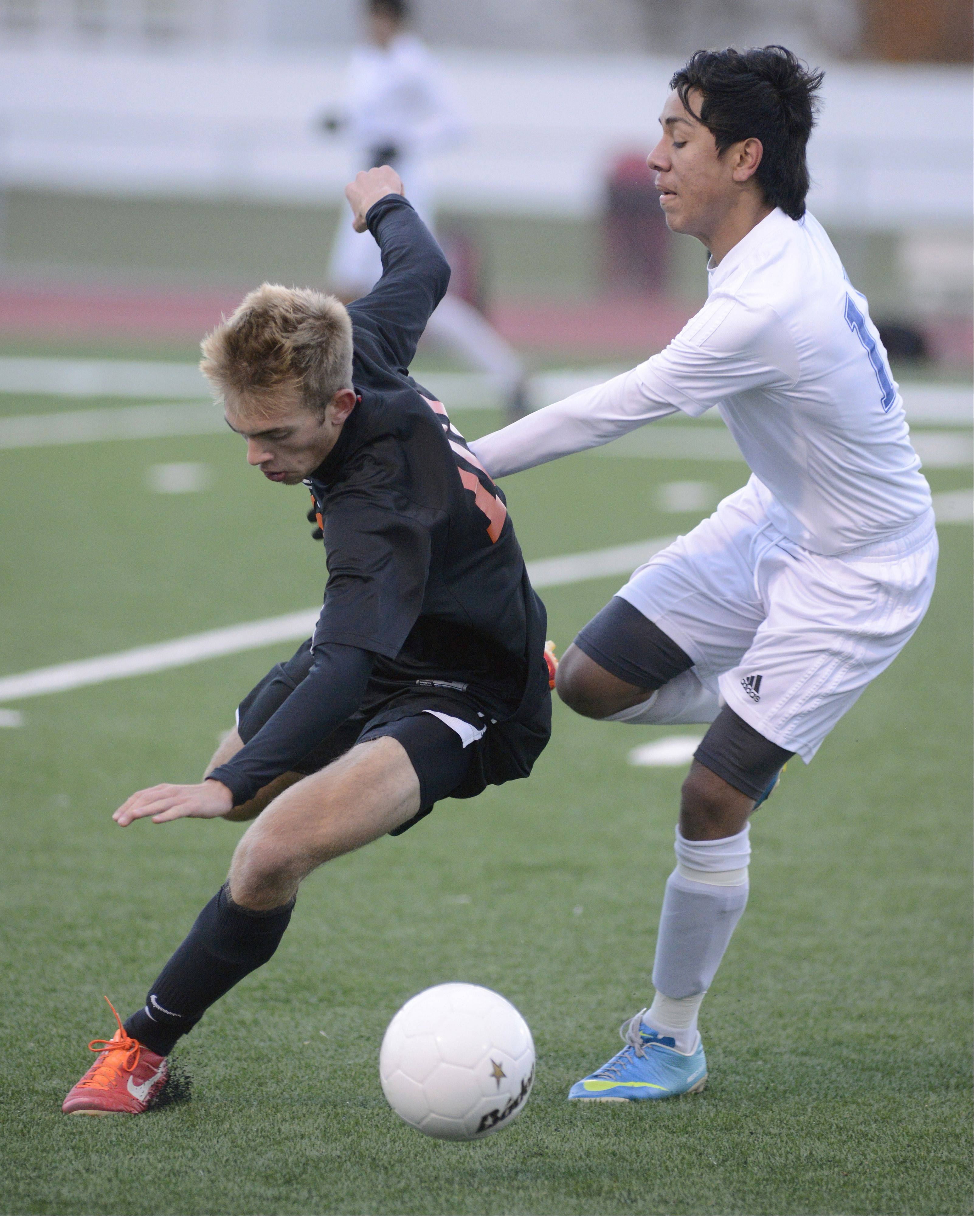McHenry's Phil Shelton and Larkin's Ricardo Nava fight for the ball, with Shelton going down in the first half of the Class 3A sectional championship at Huntley High School on Saturday, November 2.