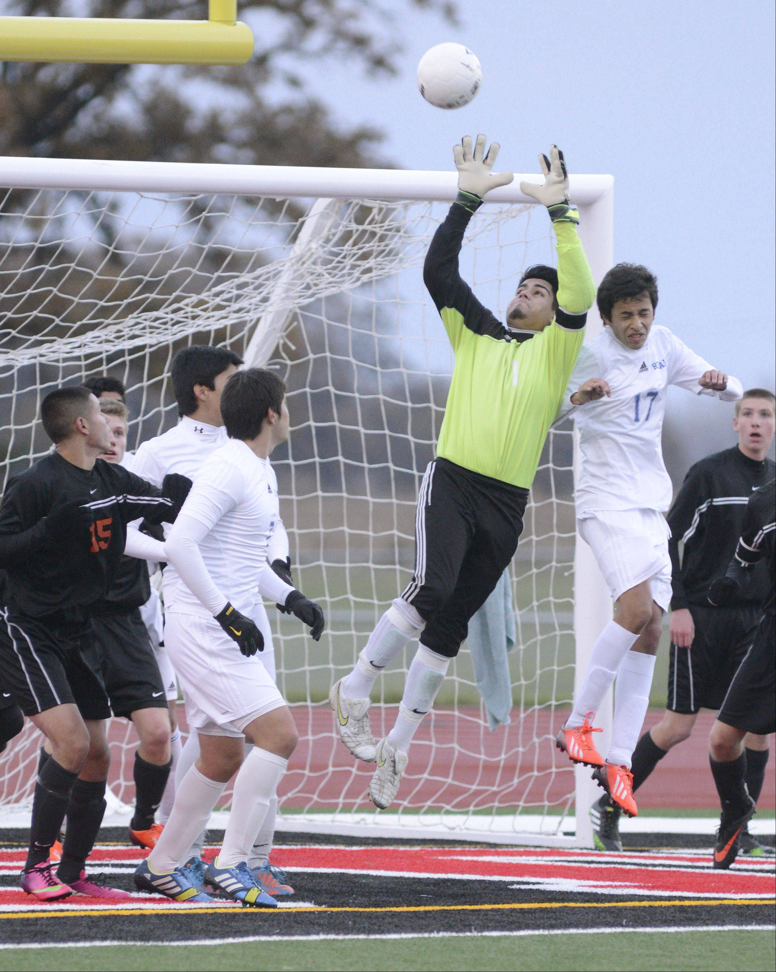 McHenry goalie Frankie Valle grabs the ball while battling Larkin's Freddy Jungo in the air for it in the first half of the Class 3A sectional championship at Huntley High School on Saturday, November 2.