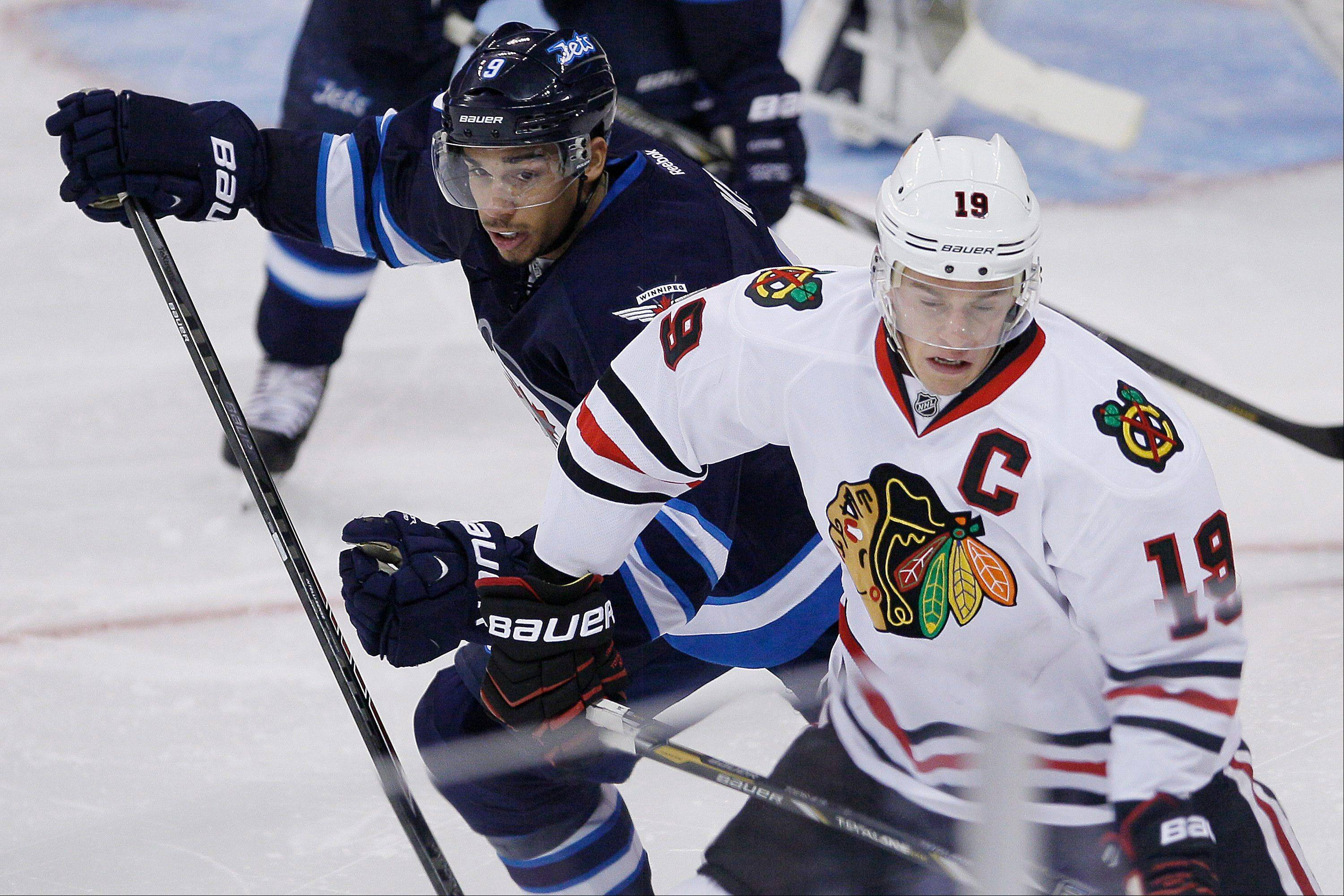Winnipeg Jets' Evander Kane (9) and Chicago Blackhawks' Jonathan Toews (19) jostle for position during the third period of an NHL hockey game in Winnipeg, Manitoba, Saturday, Nov. 2, 2013. Chicago won 5-1.
