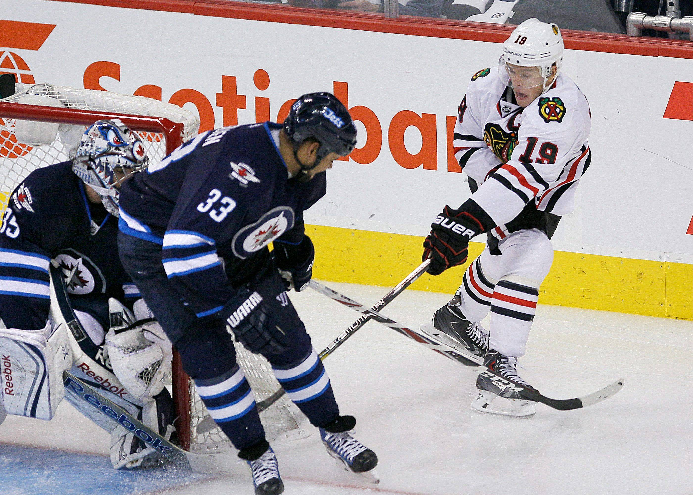 Jonathan Toews (19) attempts the wrap-around on Winnipeg Jets goaltender Al Montoya (35) as Dustin Byfuglien (33) defends during the third period of an NHL hockey game in Winnipeg, Manitoba, Saturday, Nov. 2, 2013. Chicago won 5-1.