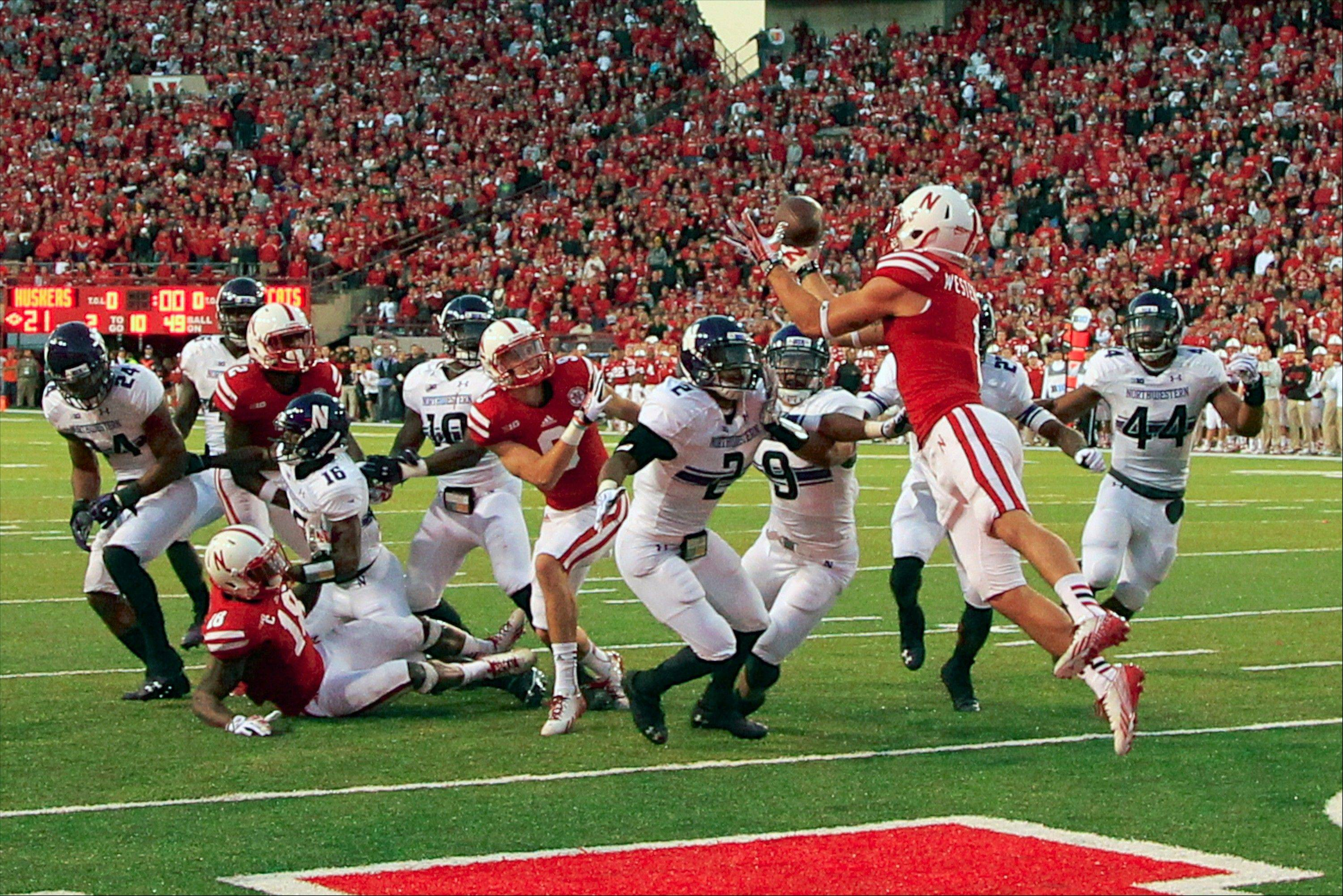 Nebraska wide receiver Jordan Westerkamp (1) catches the game-winning touchdown over Northwestern center back Dwight White (2) , safety Jimmy Hall (9) and linebacker Chi Chi Ariguzo (44) with seconds to go in the game Saturday. Nebraska won 27-24.