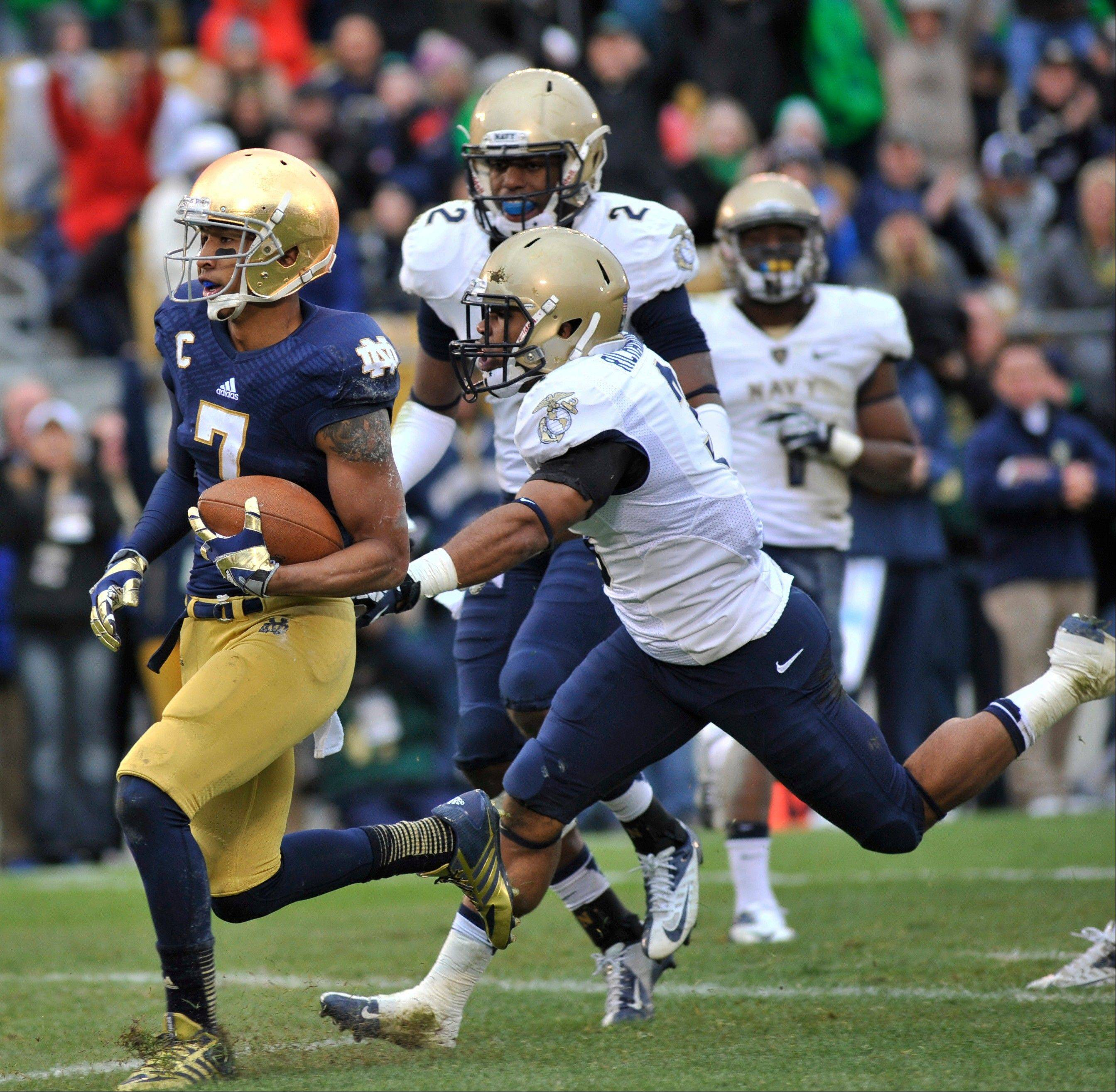 Notre Dame wide receiver TJ Jones crosses the goal line as Navy cornerback Lonnie Richardson closes in the first half in South Bend, Ind.