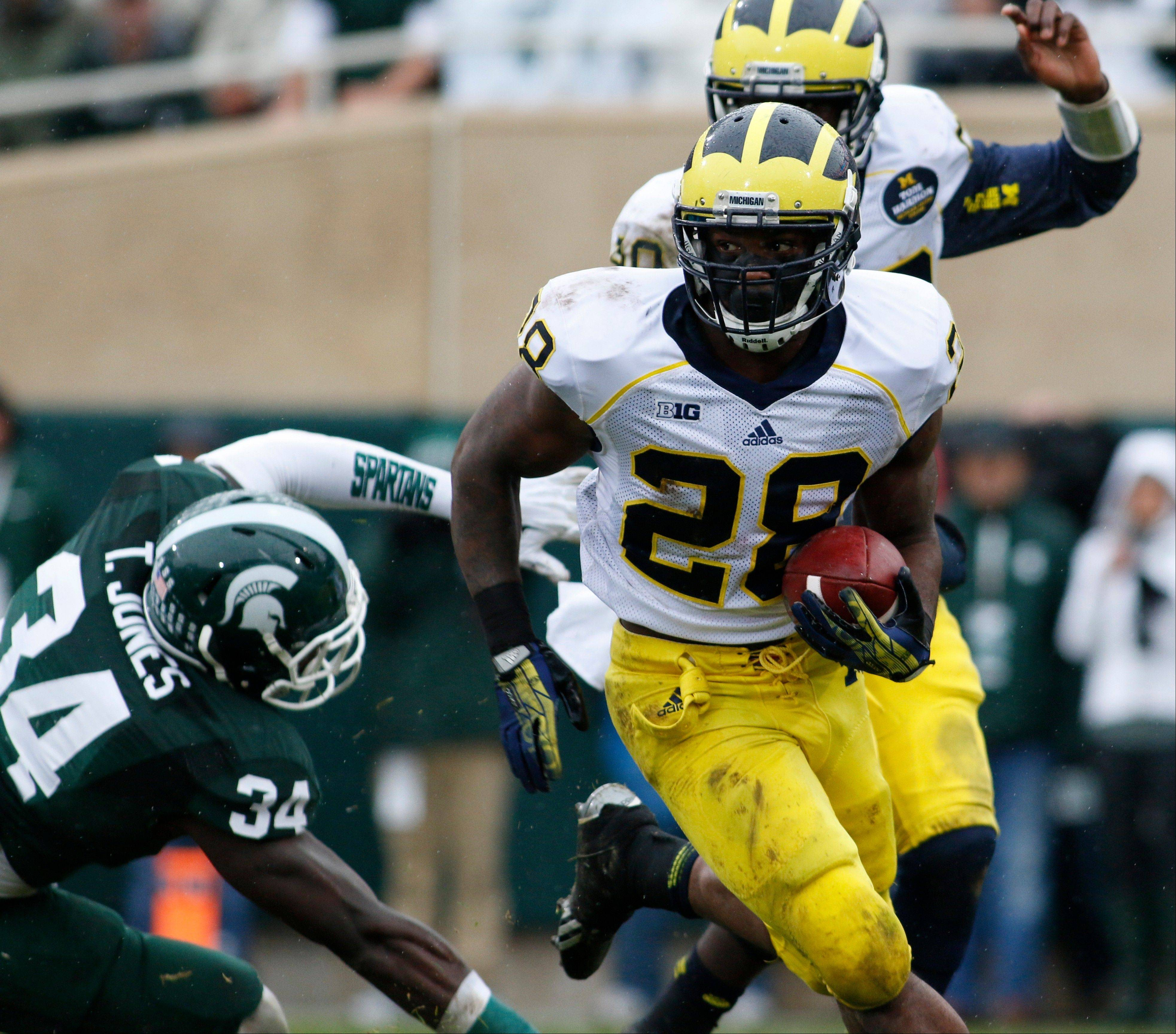 Michigan's Fitzgerald Toussaint (28) rushes against Michigan State's Taiwan Jones (34) during the first quarter.
