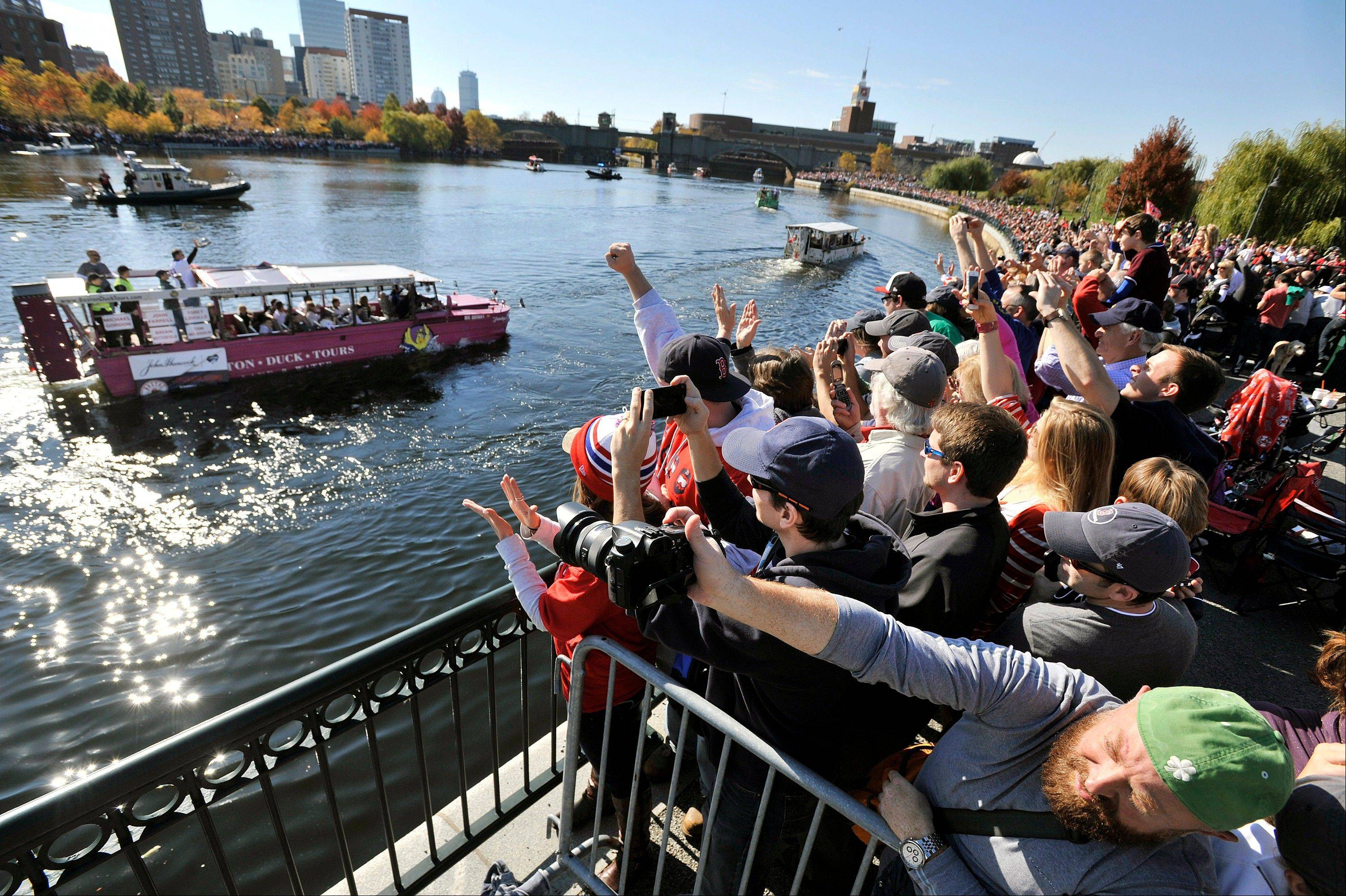 Fans gathered along the Charles River cheer as Boston Red Sox players float past on amphibious duck boats during the baseball team's World Series victory parade Saturday.