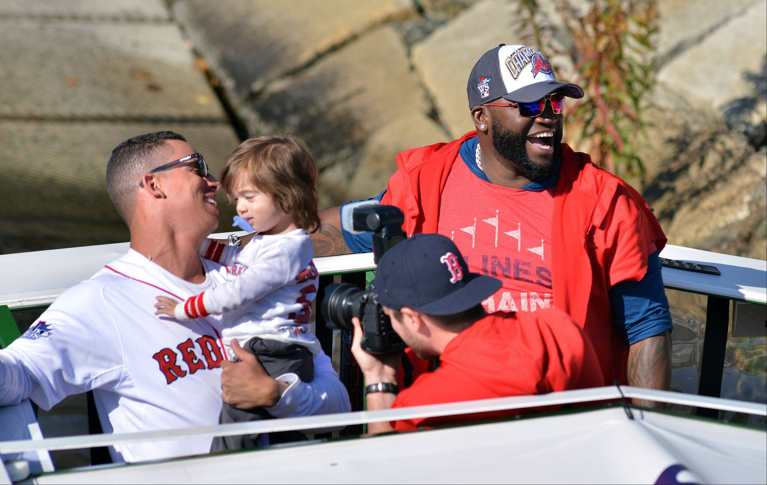 Boston Red Sox's Quintin Berry, left, and David Ortiz ride on an amphibious duck boat on the Charles River Saturday.