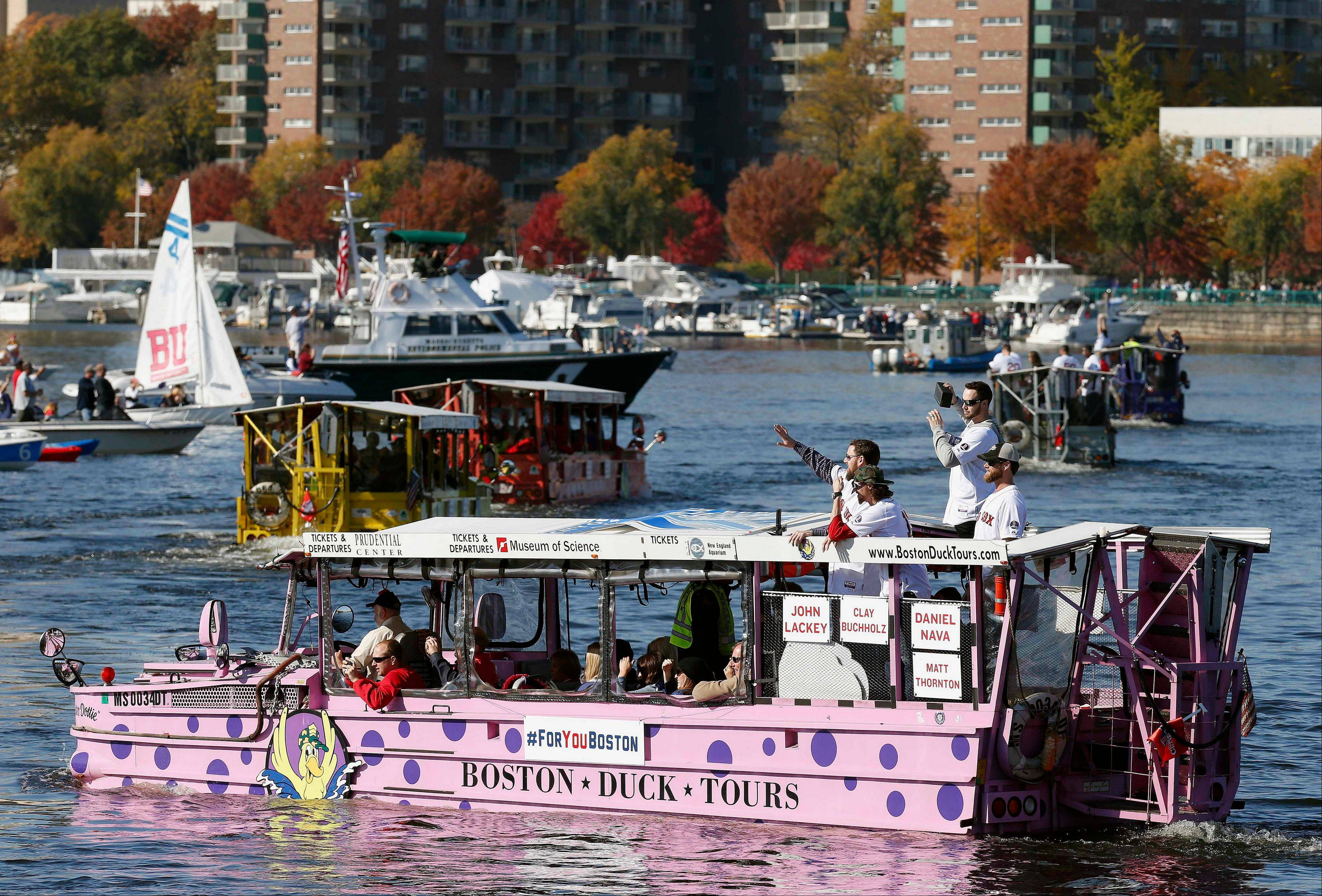 Boston Red Sox players wave from Duck Boats on the Charles River during a rolling victory parade celebrating the team's World Series title.