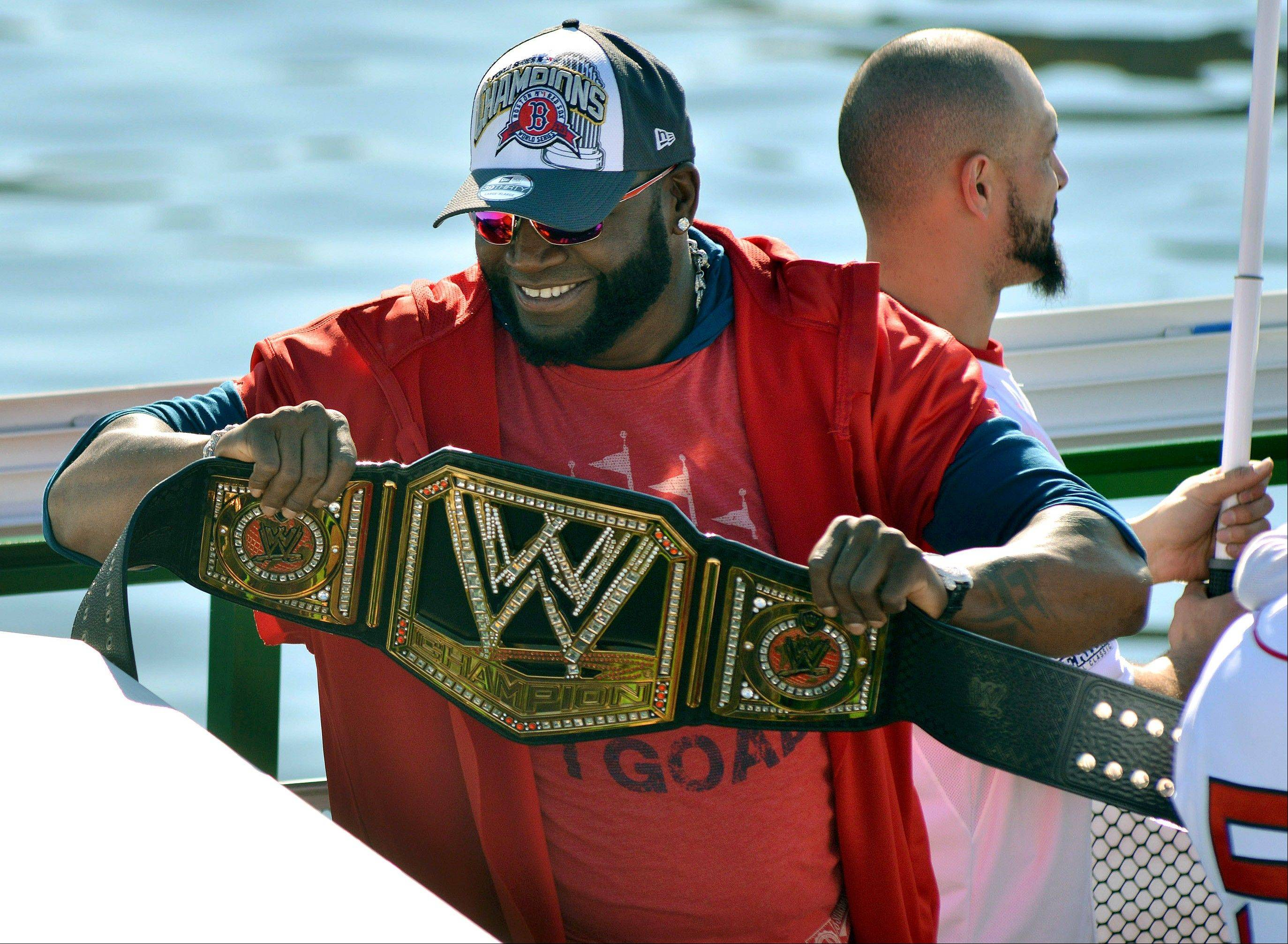Boston Red Sox' David Ortiz holds up a championship belt as he and fellow players ride on a duck boat.rolling parade celebrating the team's World Series title.