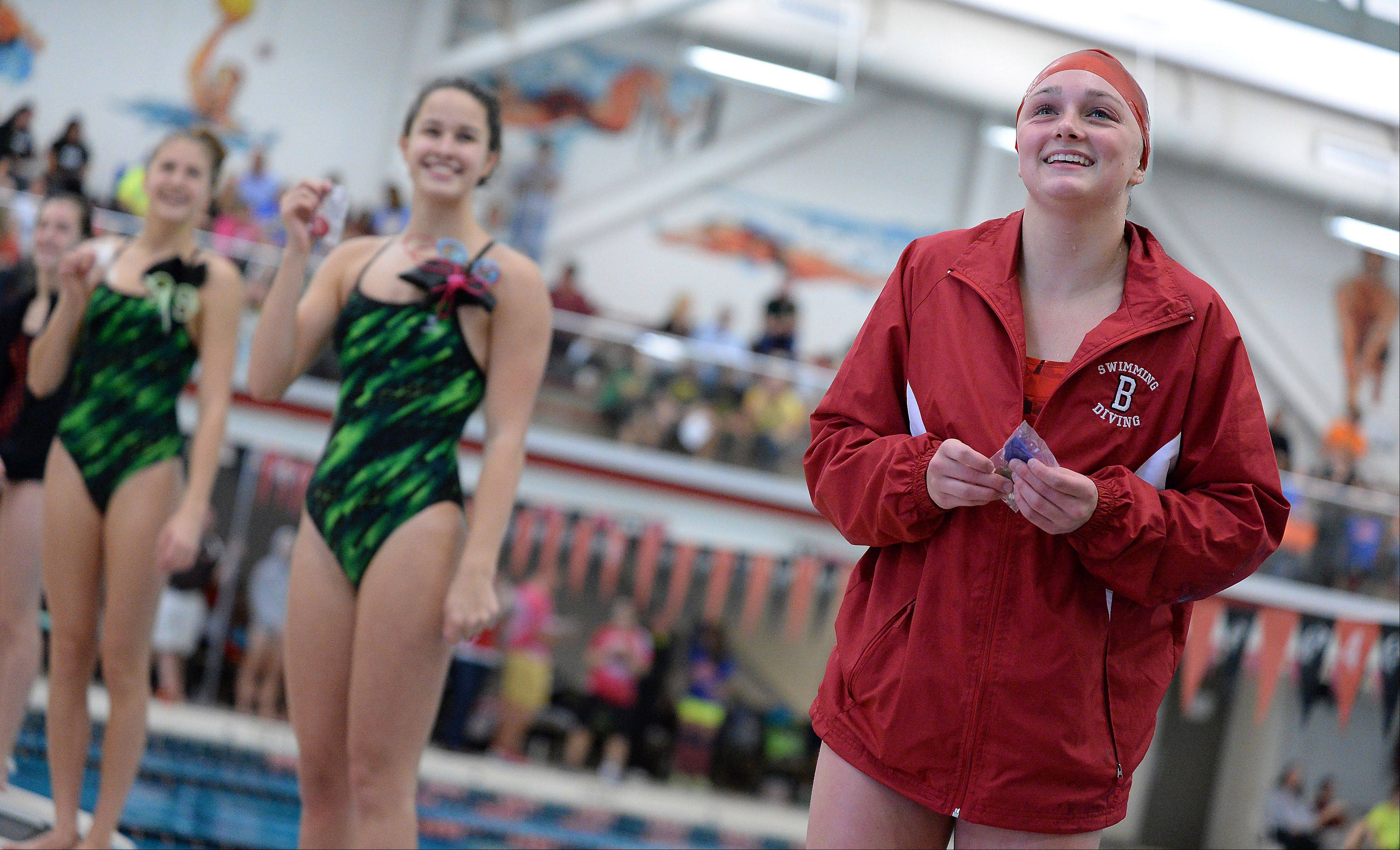 Barrington's Mekenna Scheitlin stands in victory row with a first place in the girls 100-yard freestyle at the Mid-Suburban League championships in Barrington on Saturday.