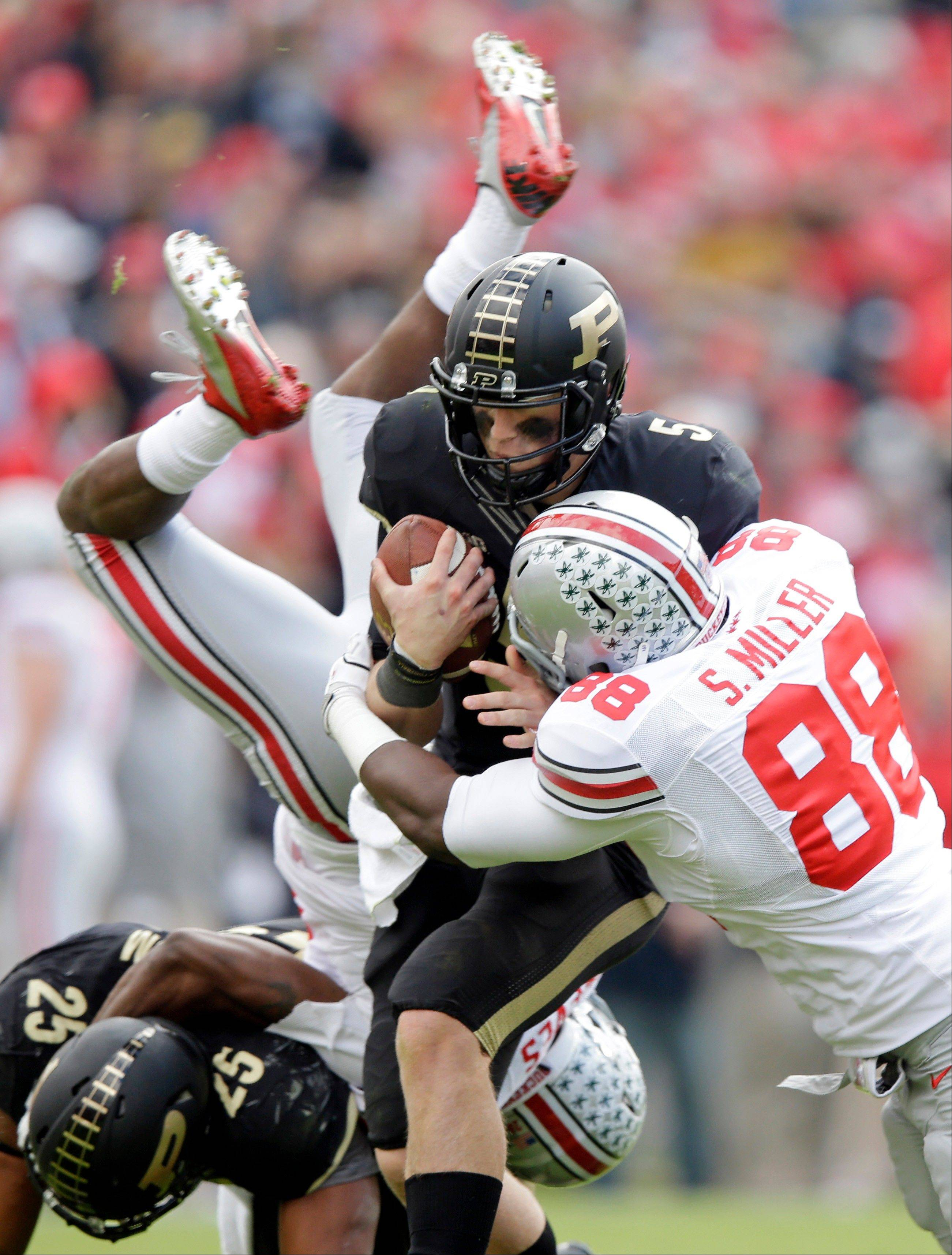 Purdue quarterback Danny Etling is sacked by Ohio State defensive lineman Steve Miller (88) as Ohio State cornerback Armani Reeves flips over Purdue running back Brandon Cottom during the second half Saturday in West Lafayette, Ind.