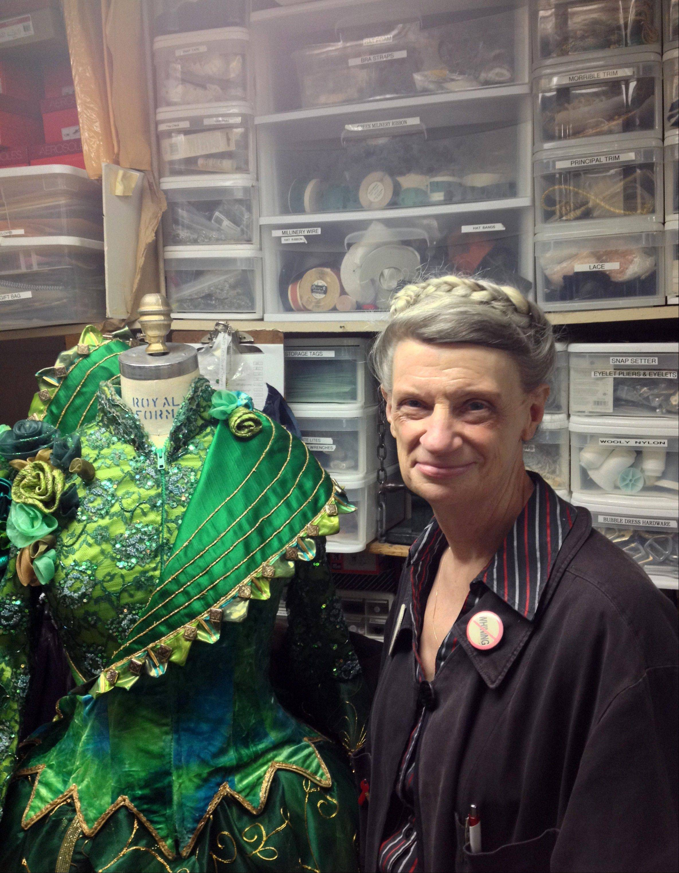 Alyce Gilbert, production wardrobe supervisor at Broadway�s �Wicked,� shows one of the costumes in the show at the Gershwin Theatre in New York. Gilbert has been working backstage at the musical since its out-of-town tryouts in San Francisco in 2003.