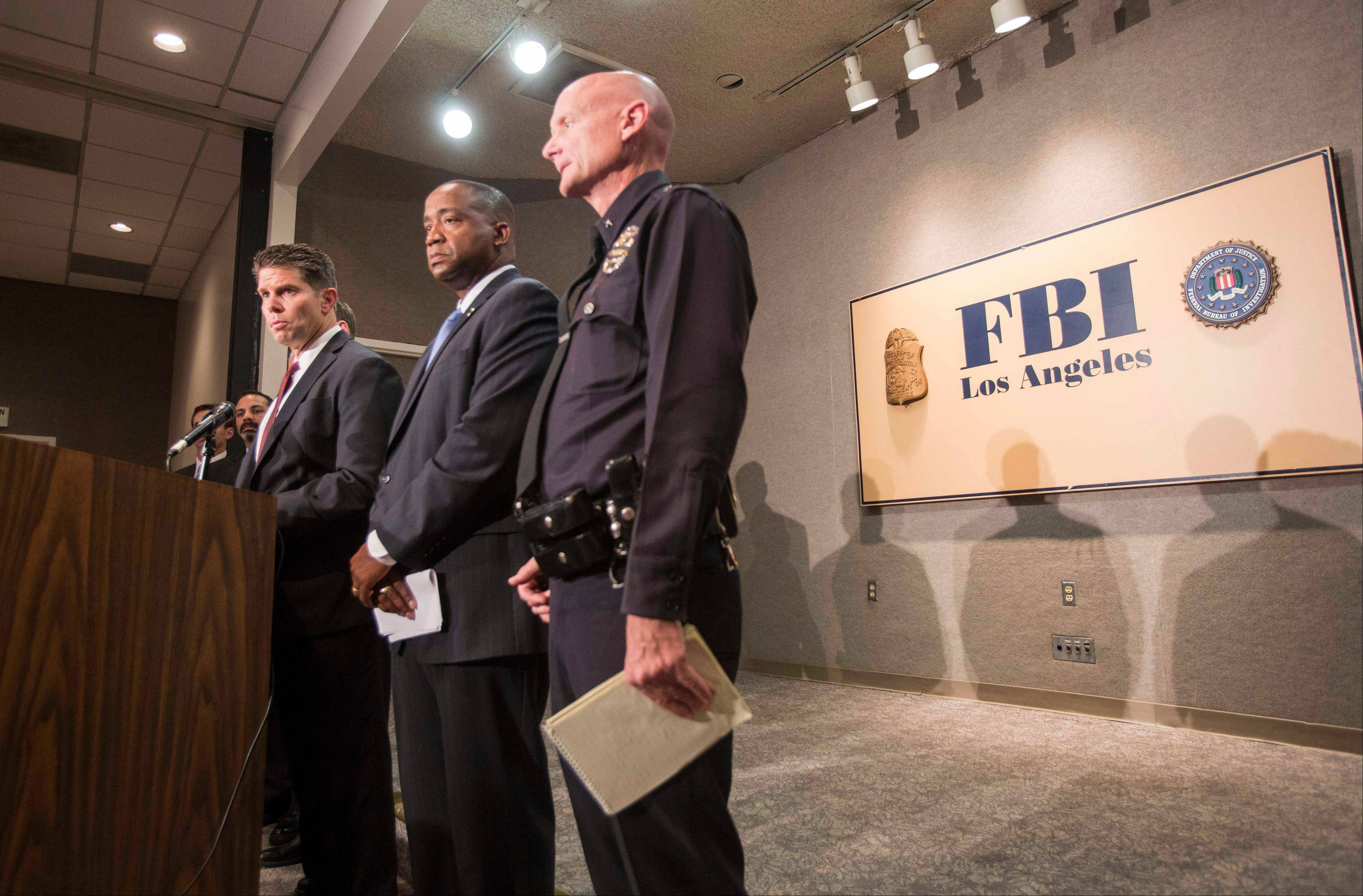 From left to right, FBI Special Agent in Charge David L. Bowdich, U.S. Attorney Andre Birotte Jr. and Los Angeles Police Department Commander Andrew Smith provide an update Saturday on the investigation into the shooting Los Angeles International Airport.