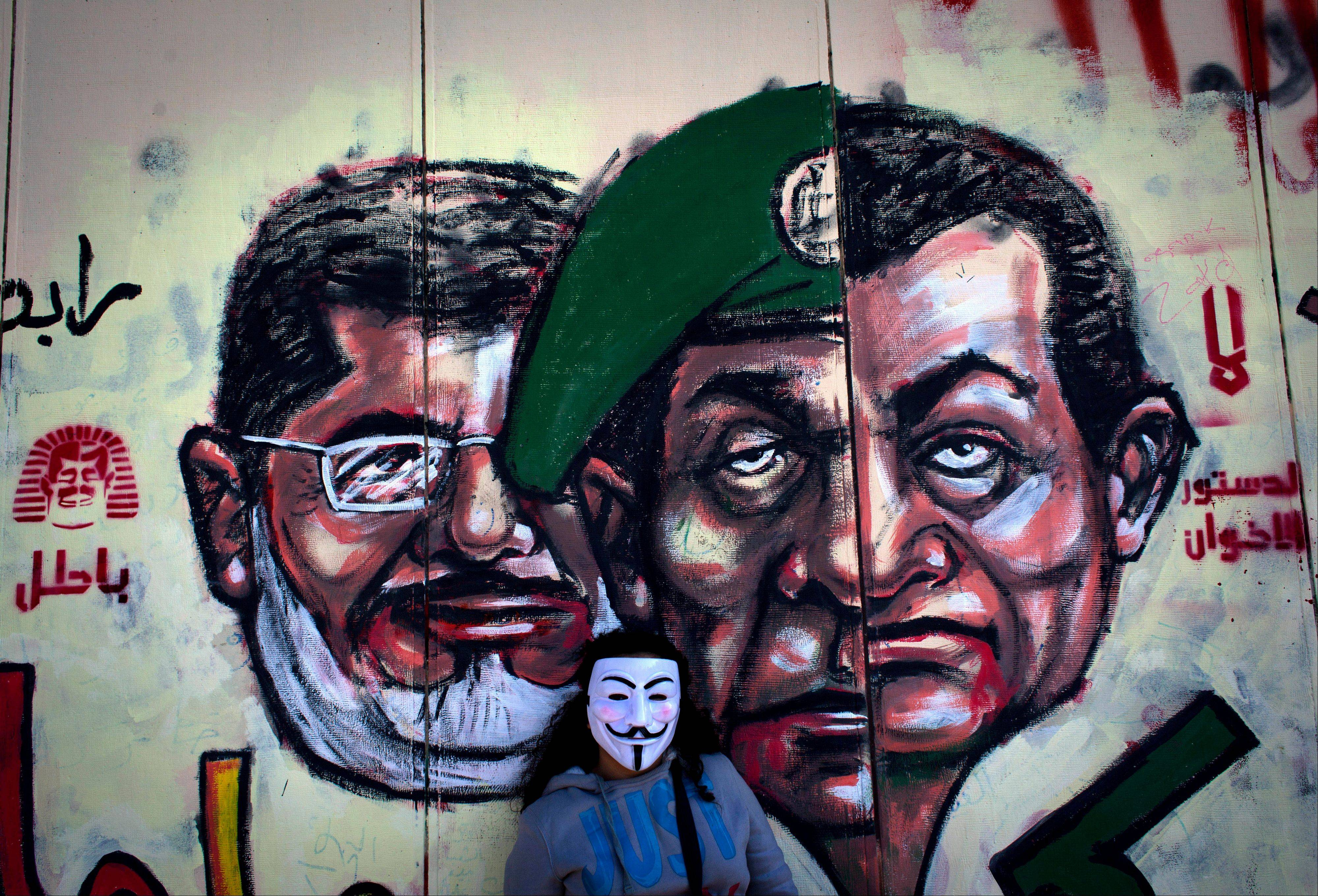 In this file photo from Dec. 8, 2012, an Egyptian protester poses next to a mural painted overnight on the exterior wall of the presidential palace depicting president Mohammed Morsi, left, former military council ruler Hussein Tantawi, center and ousted President Mubarak with Arabic that reads �No, the brotherhood�s constitution is not valid,� in Cairo. Morsi goes on trial Monday.