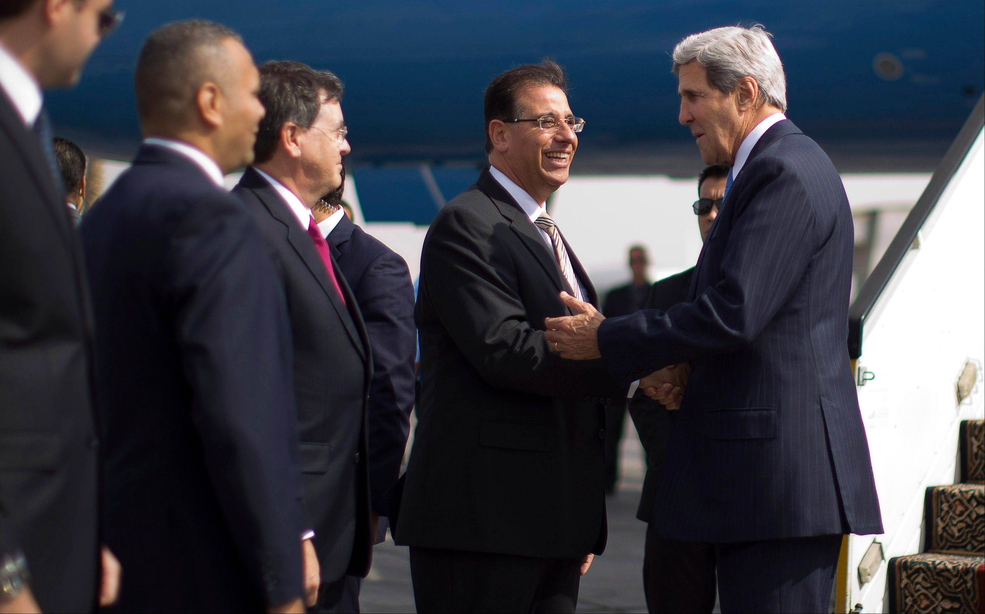 Secretary of State John Kerry, right, is greeted by Egypt�s Ambassador Farid Munib, chief of protocol, in Cairo Sunday. Kerry is in Cairo pressing for reforms during the highest-level American visit to Egypt since the ouster of the country�s first democratically elected president.