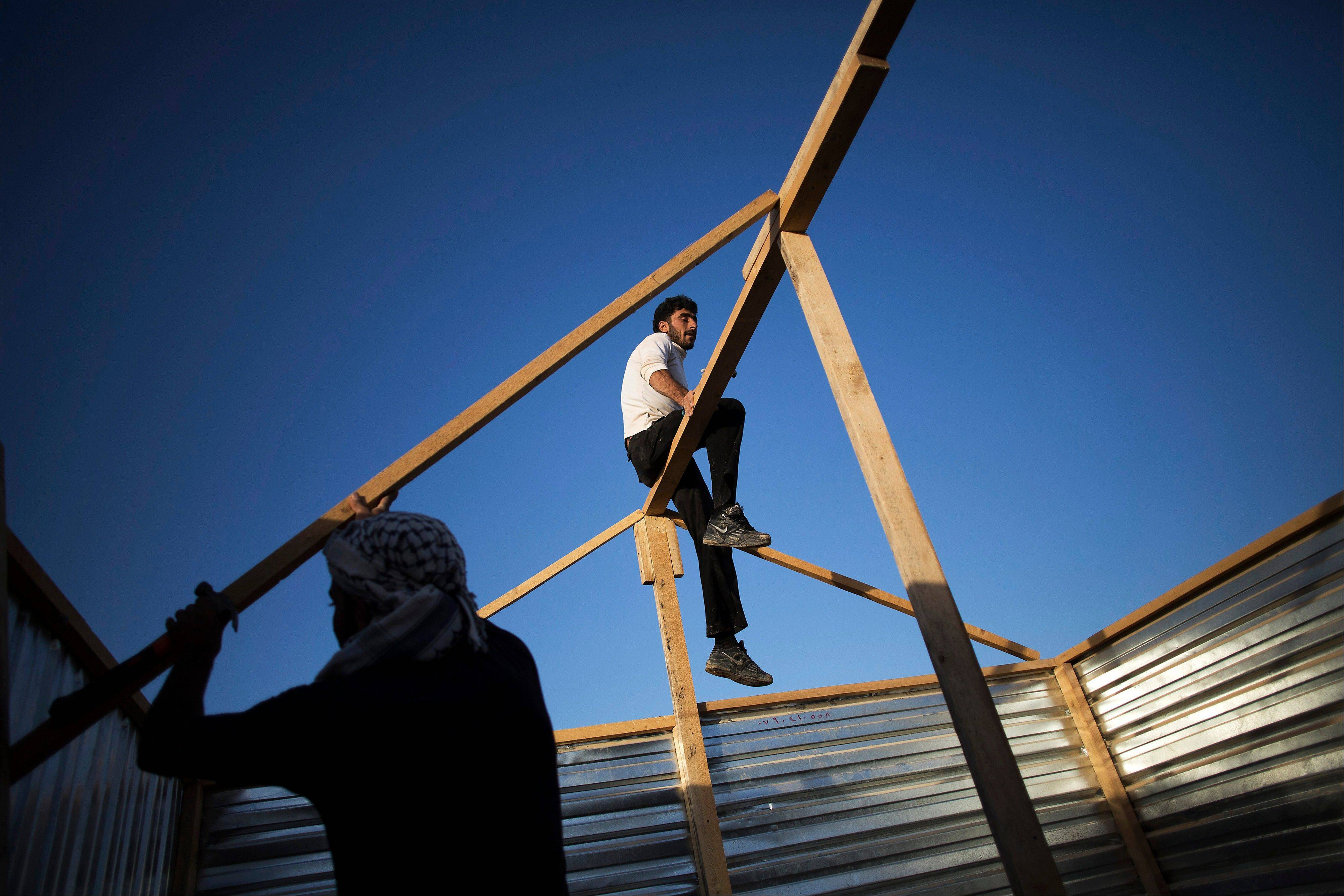 Syrian refugees build a makeshift house at the Zaatari refugee camp near the Syrian border in Jordan. With Syria�s civil war in its third year, more than 2 million Syrians have fled their country. About 100,000 live in this camp.