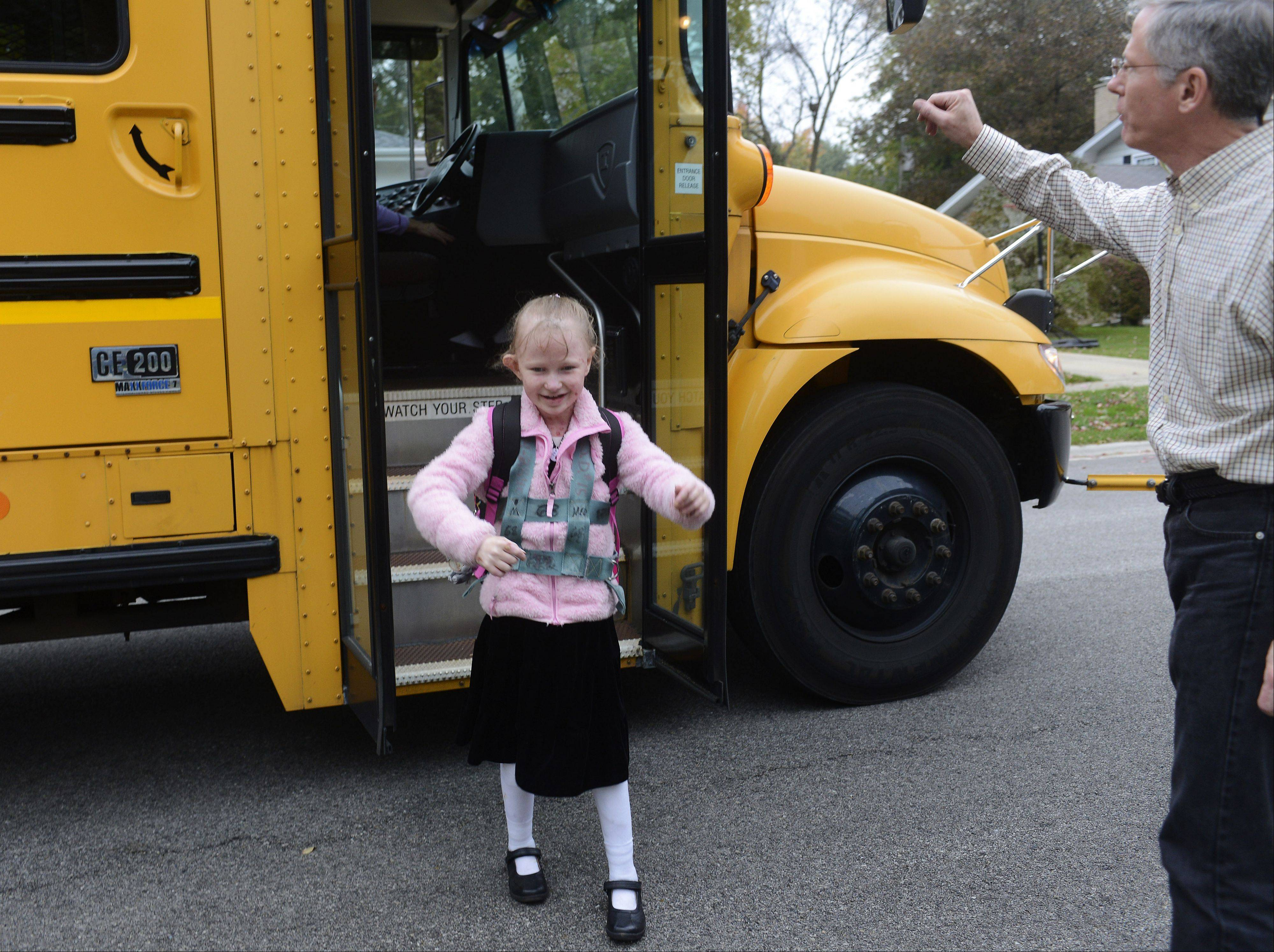 Stepping off the bus after a day of school, Caroline Provost, 8, is greeted by her dad, Pete Provost, outside their Palatine home.
