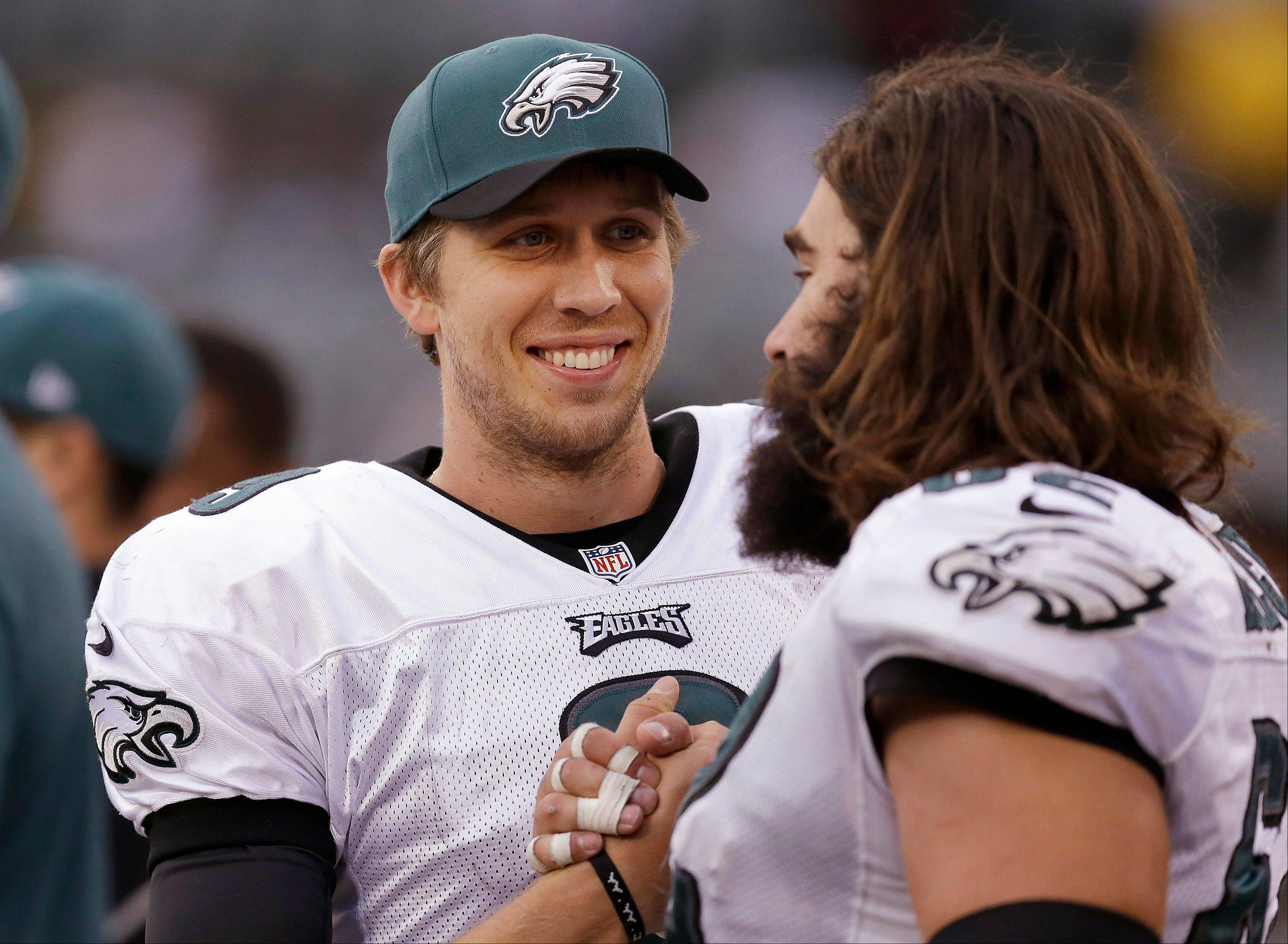 Philadelphia Eagles quarterback Nick Foles, left, smiles as he celebrates with center Jason Kelce during the fourth quarter of an NFL football game against the Oakland Raiders in Oakland, Calif., Sunday, Nov. 3, 2013. The Eagles won 49-20.