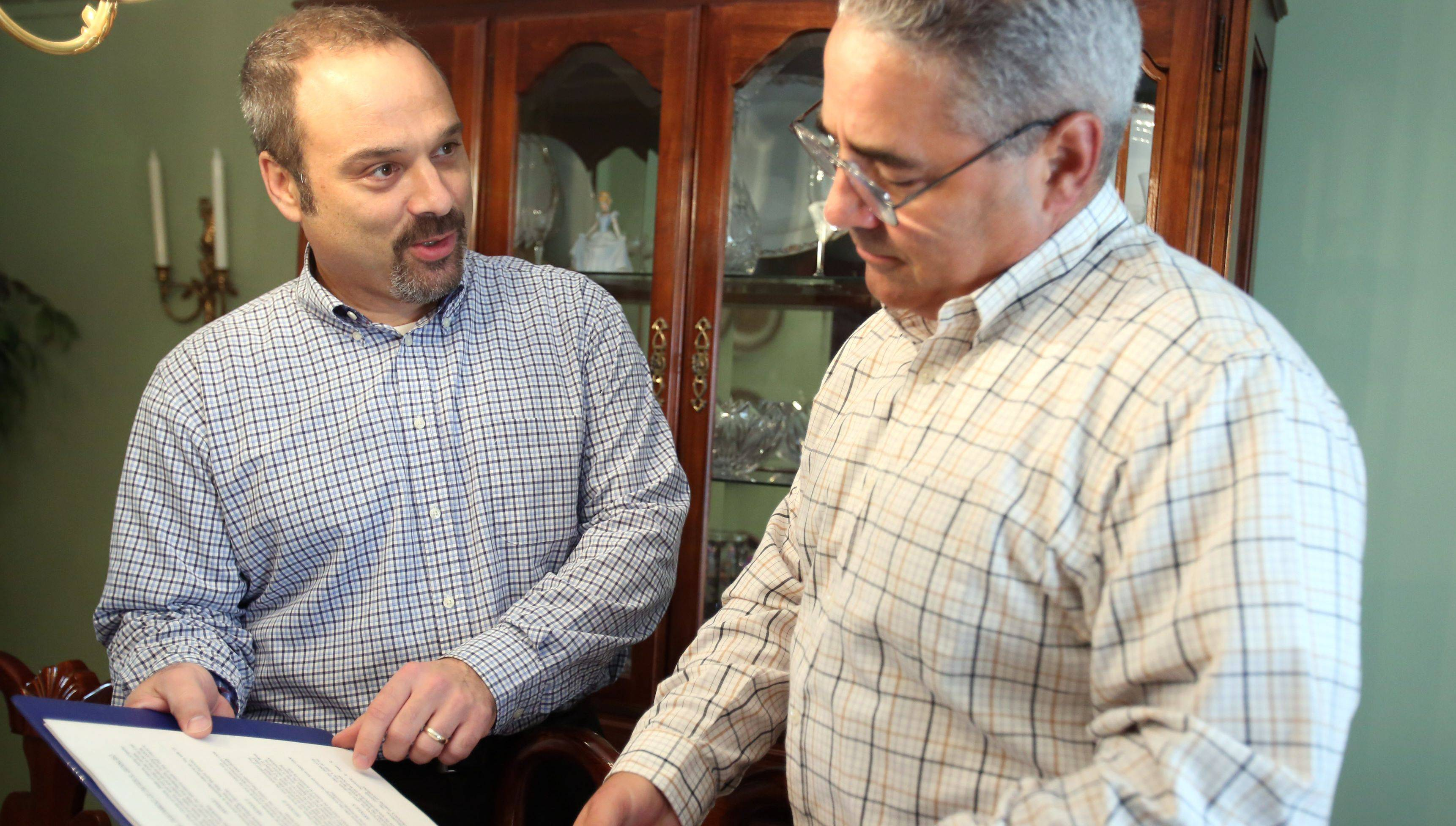 Paul Gennuso, left, a lawyer and partner of Gennuso Financial Group, reviews plans with his brother Peter.