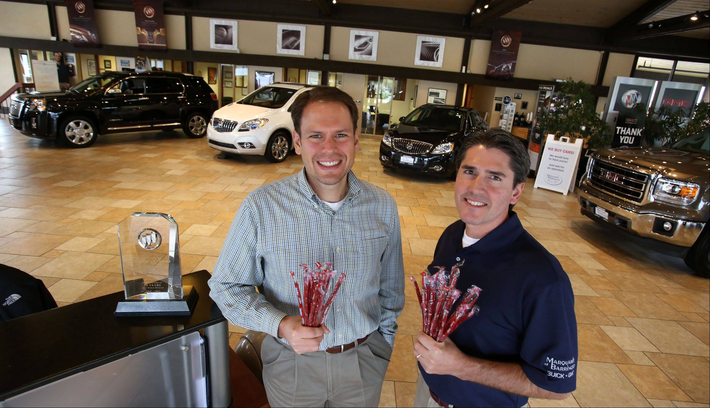 Marquardt of Barrington owners Dan Marquardt, left, and Kurt Marquardt hold licorice, a tradition started by their father, Larry, who kept the showroom stocked with the candy to give to the dealership's customers.