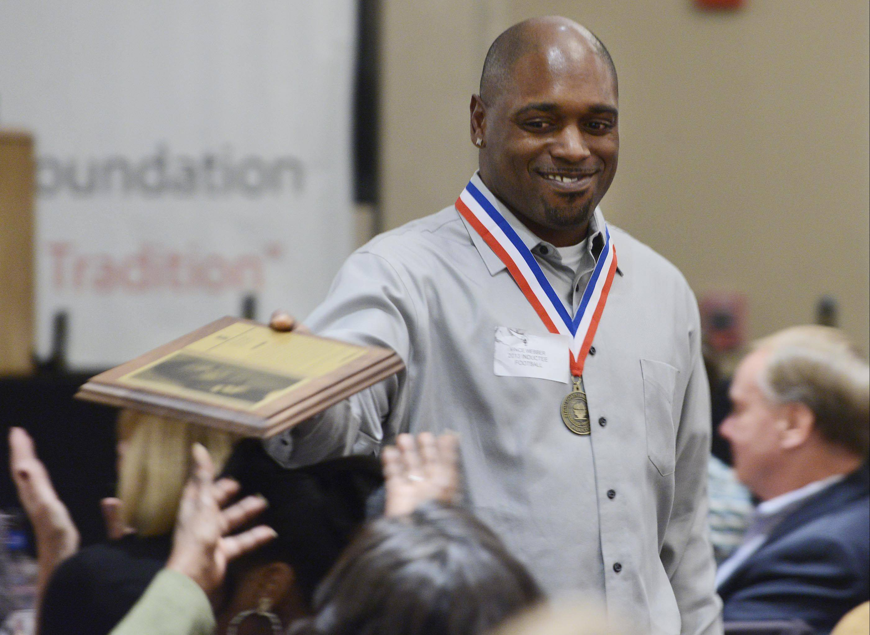 Vince Webber, a 1998 Larkin High School graduate, hands his plaque to his family Sunday during the 34th Induction Ceremony of the Elgin Sport Hall of Fame at The Centre of Elgin. He set several school records for football statistics.