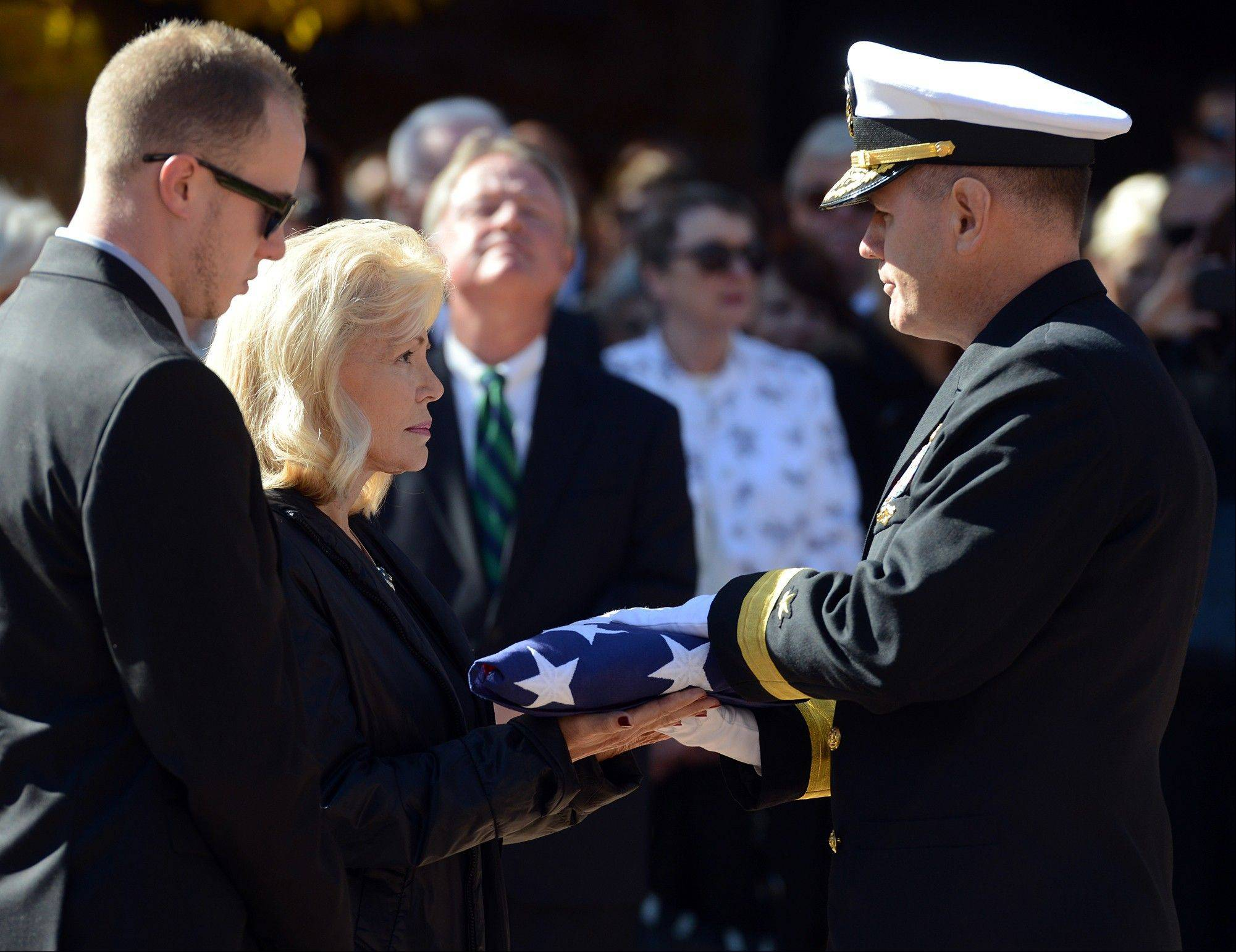 Patty Carpenter, left, receives the flag that was draped over her husband, astronaut Scott Carpenter's casket from U.S. Navy Rear Adm. Thomas Bond on Saturday, Nov. 2, 2013, in Boulder, Colo. Carpenter was the second American to orbit the Earth, following John Glenn.