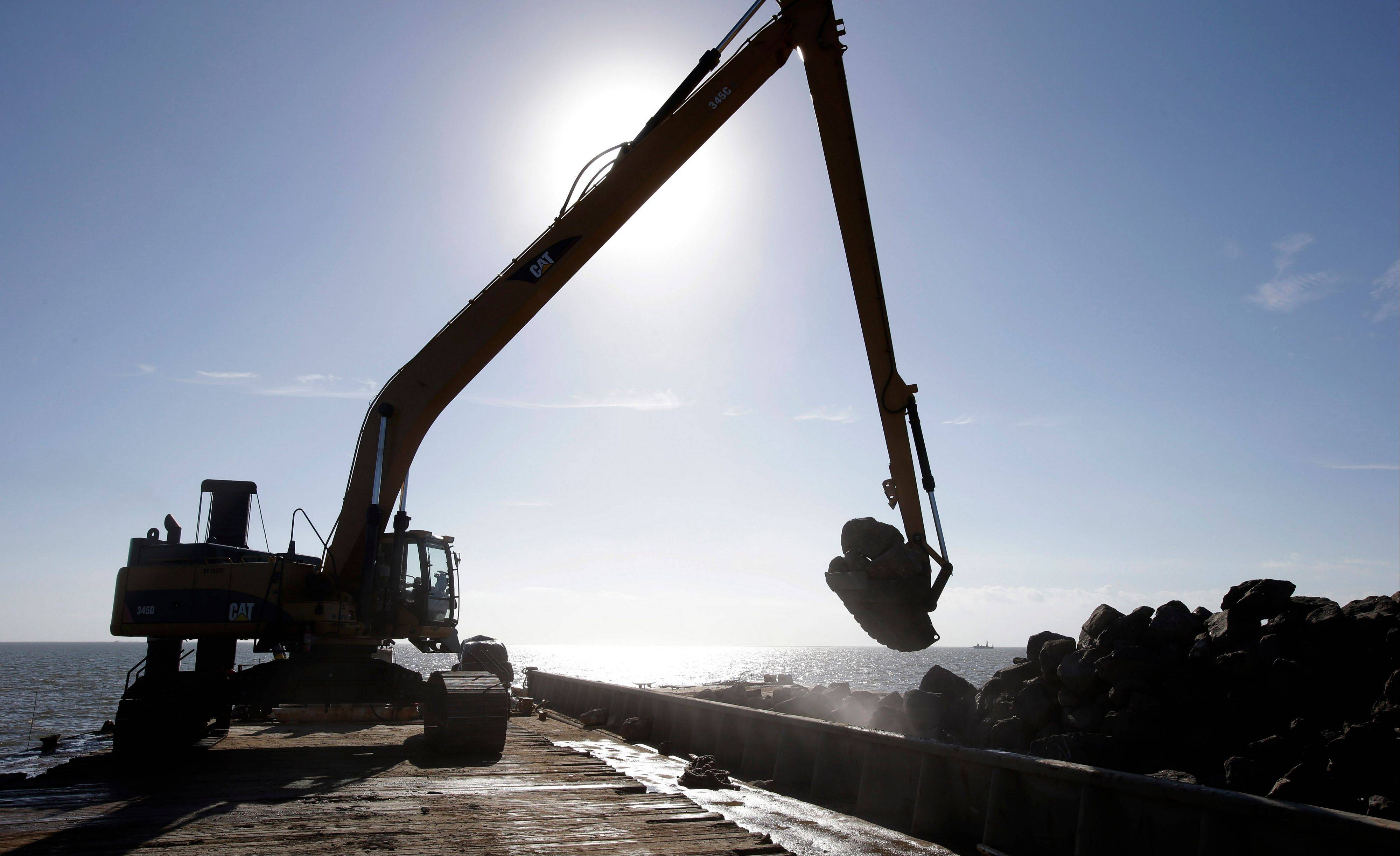 A large excavator is silhouetted as it scoops up a load of limestone boulders from a barge in the Gulf of Mexico off the Texas coast on Tuesday, Oct. 29, 2013. The huge boulders will be dropped into the water to help rebuild a reef that once filled some 400 acres and now barely exists.