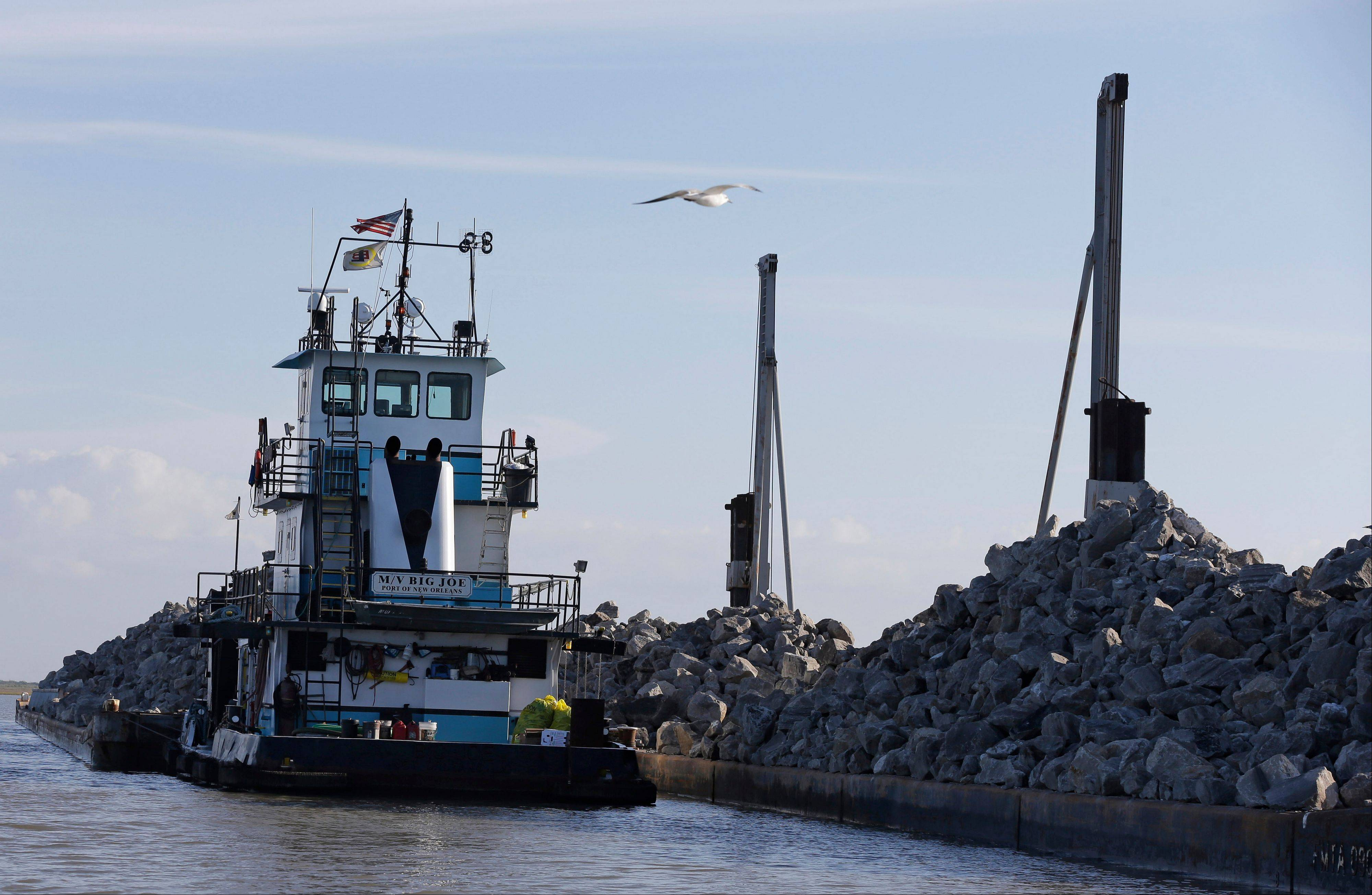 A bird flies past a tug boat abutting barges filled with limestone boulders on Tuesday, Oct. 29, 2013 in the Gulf of Mexico. The boulders will be dropped into the water off the Texas coast in one of the largest oyster reef restoration projects in the United States.