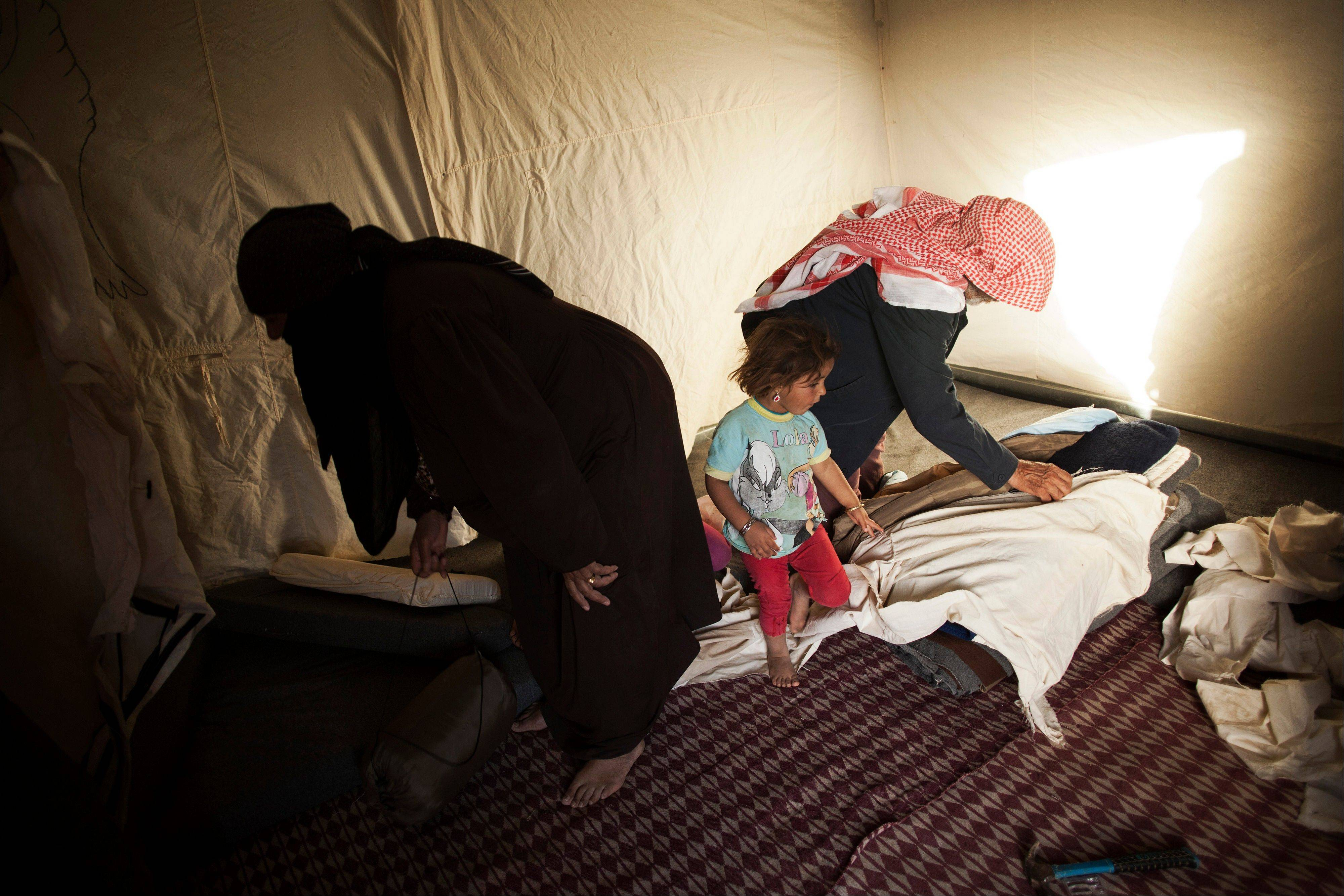 Syrian refugees work in their makeshift shelter while their granddaughter plays around them at the Zaatari refugee camp near the Syrian border in Jordan.