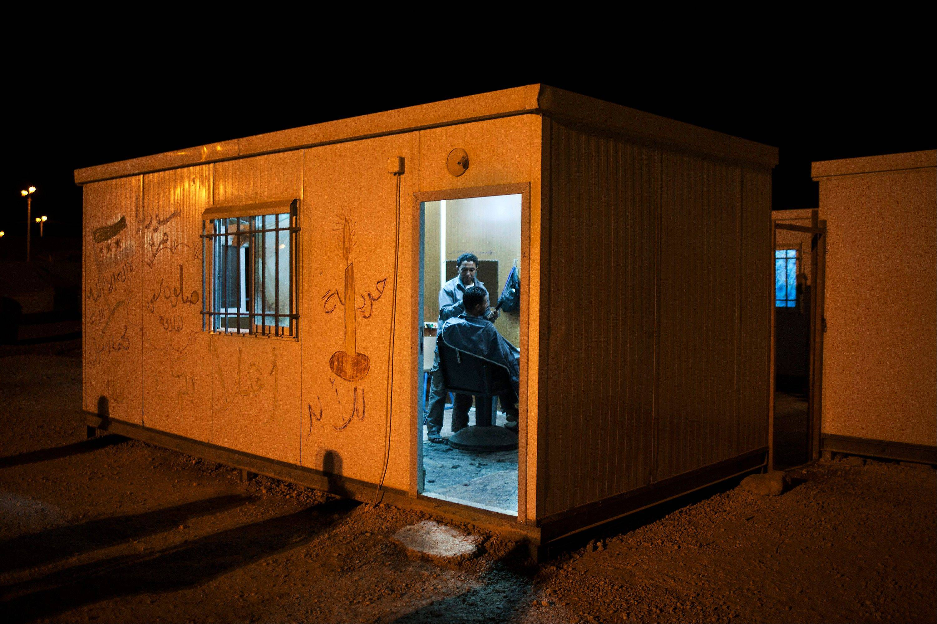 A hairdresser works at his trailer at the Zaatari refugee camp near the Syrian border in Jordan.