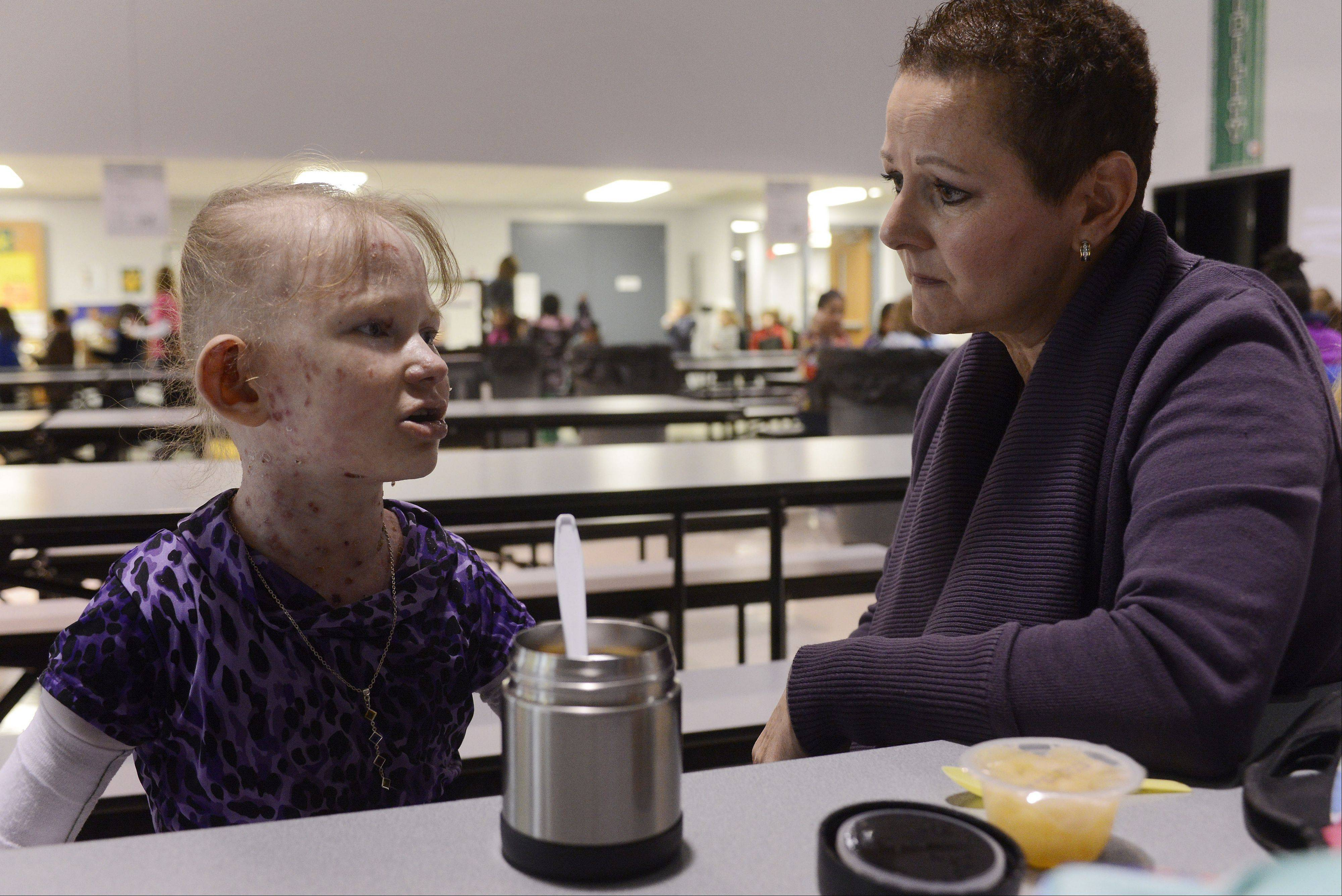 Having developed a true friendship during their three years together, Caroline Provost, 8, talks with Michelle Whiteside, her one-on-one program assistant, as lunch begins at Kimball Hill School in Rolling Meadows.