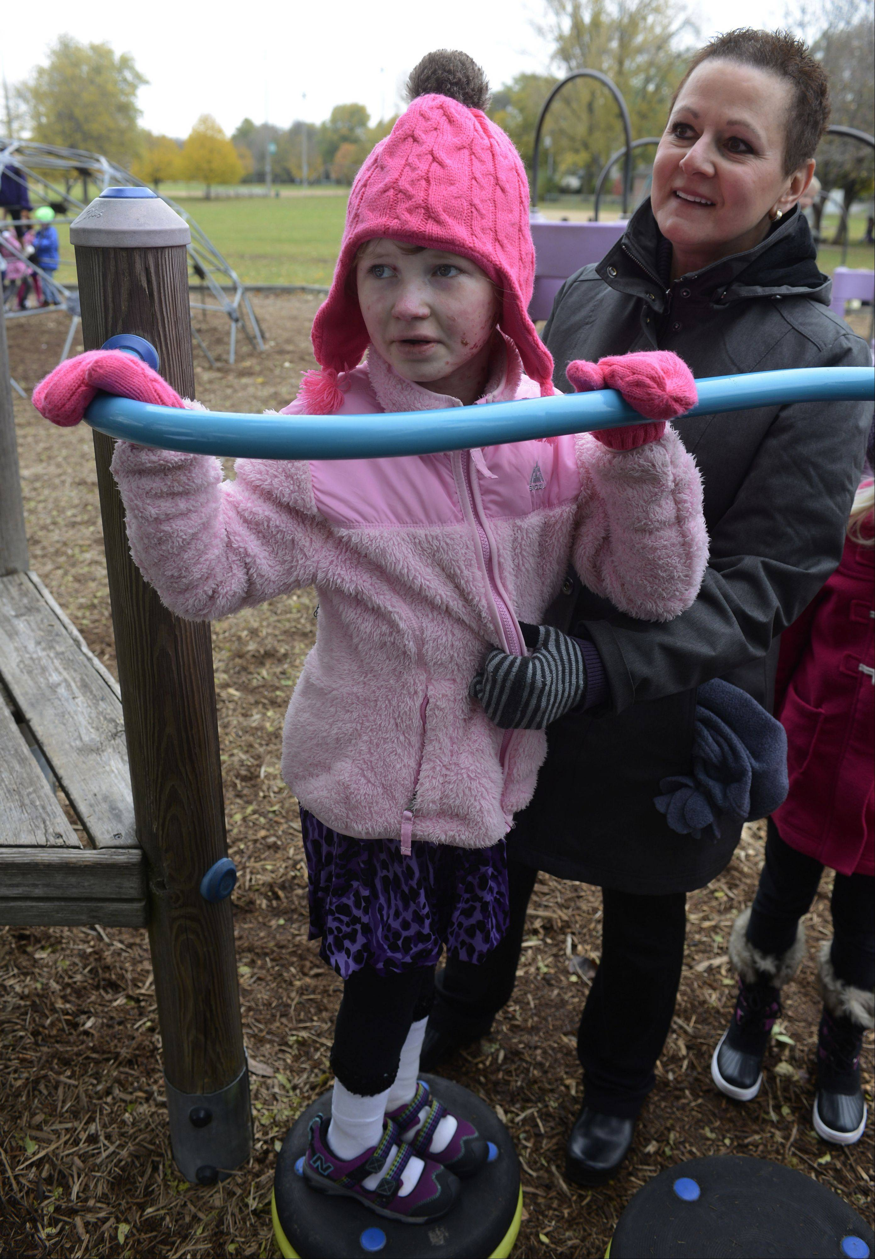 As Caroline Provost twists on a fun piece of playground equipment at recess, aide Michelle Whiteside gently grabs her coat. Because of a rare genetic disorder, even a mild bump can blister and tear the girl's skin.