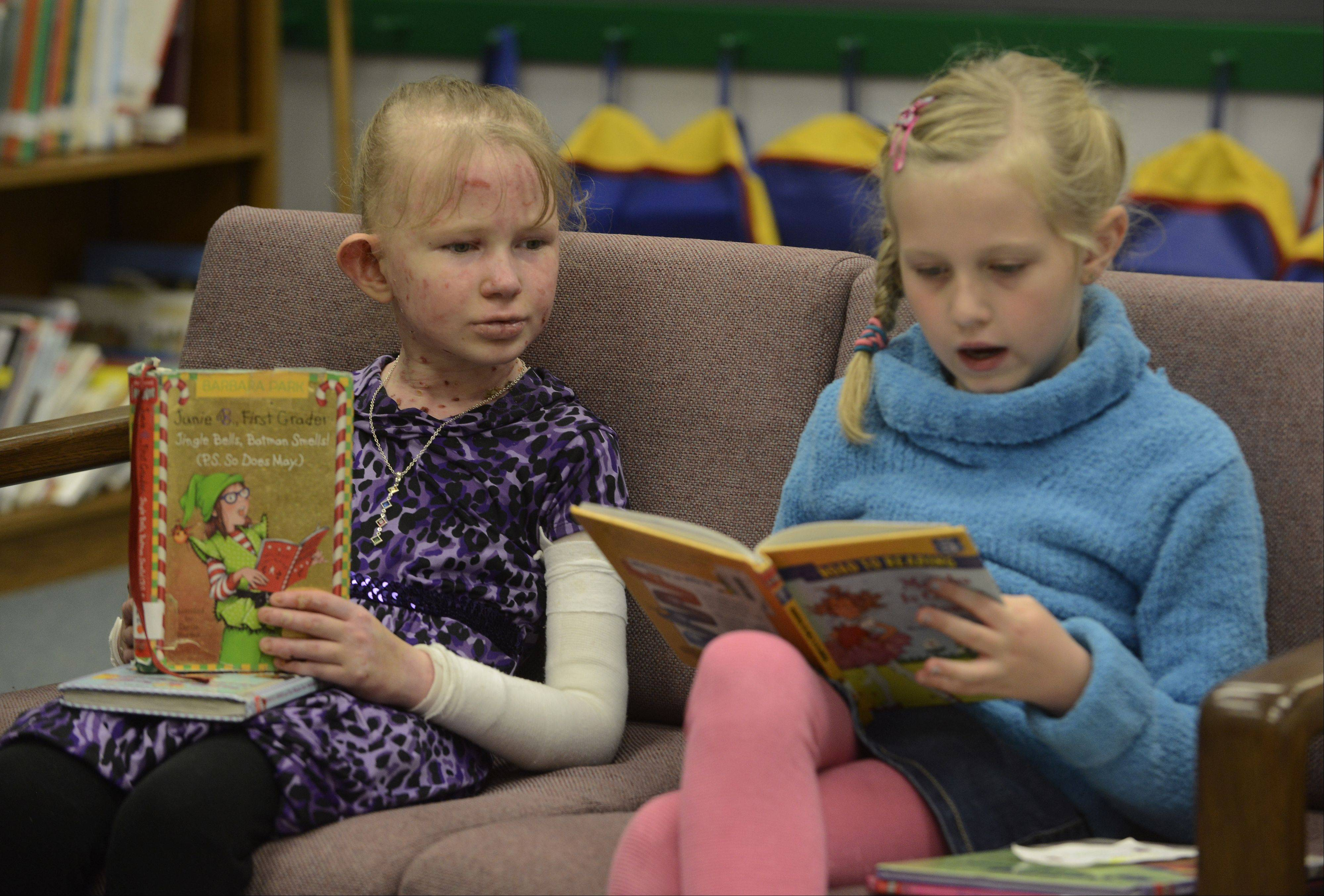 Second-grader Caroline Provost reads with friend Cece Gary at Kimball Hill School in Rolling Meadows.