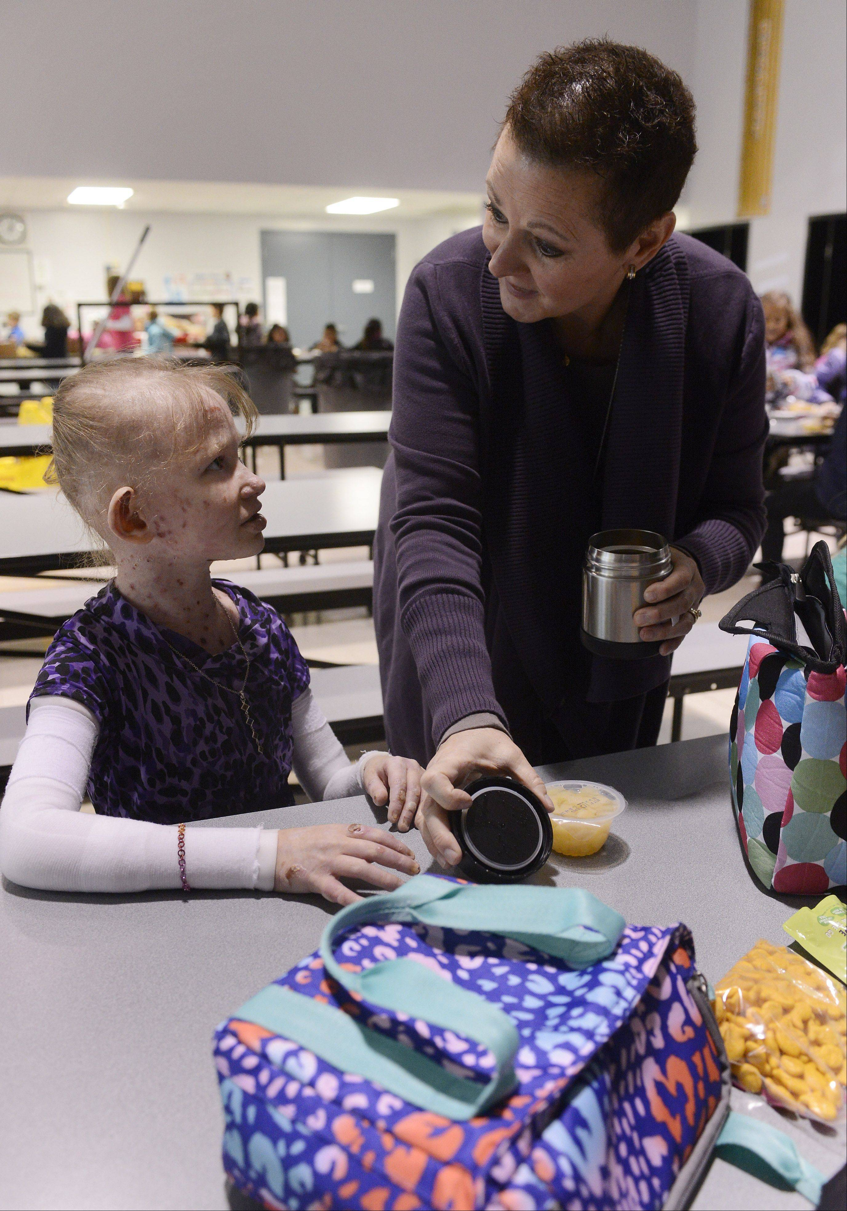 Caroline Provost gets ready for lunch with the help of one-on-one program assistant Michelle Whiteside at Kimball Hill School in Rolling Meadows.