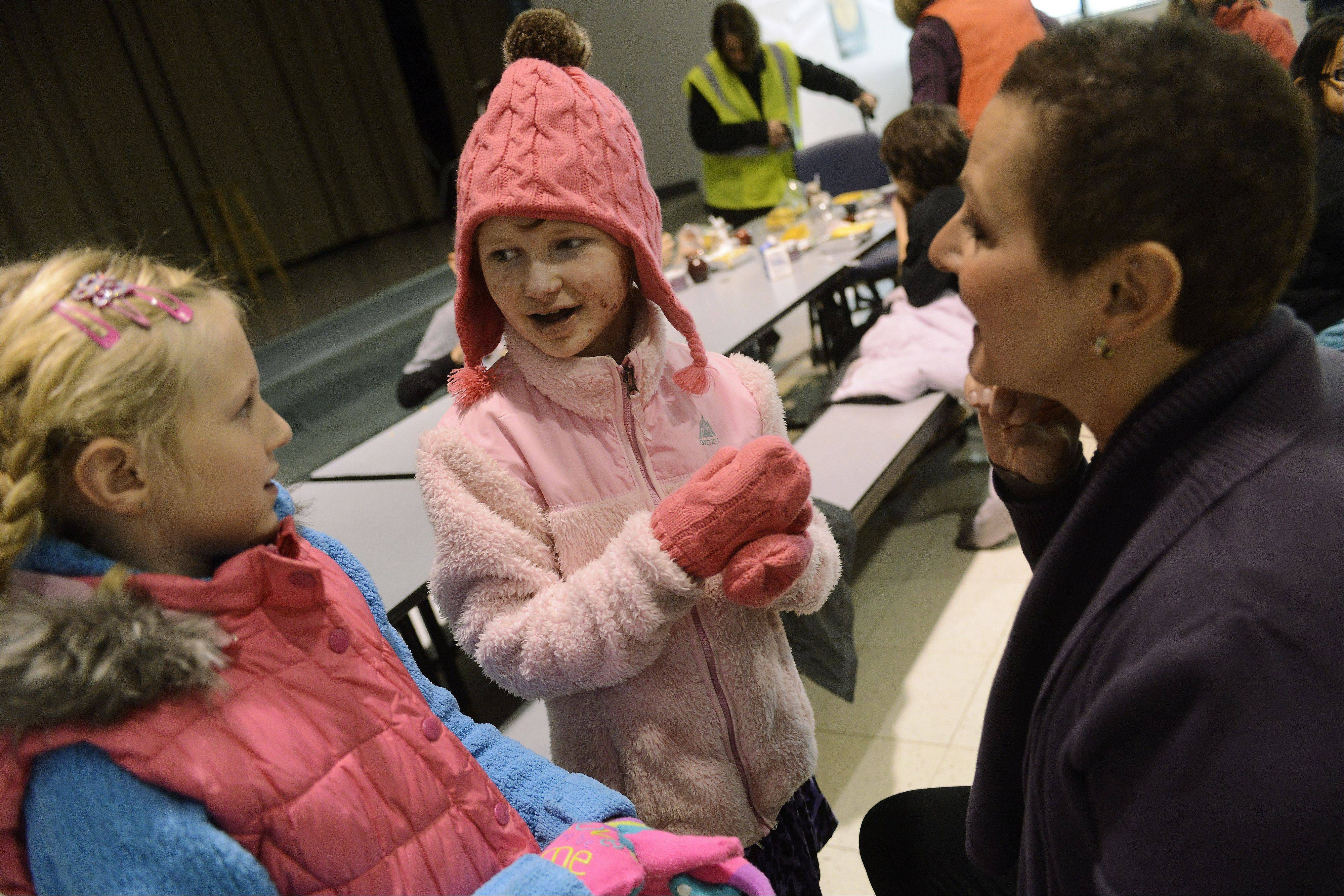 Deciding to hit the swings first, Caroline Provost, center, chats with friend Cece Gray and one-on-one program assistant Michelle Whiteside at Kimball Hill School in Rolling Meadows.
