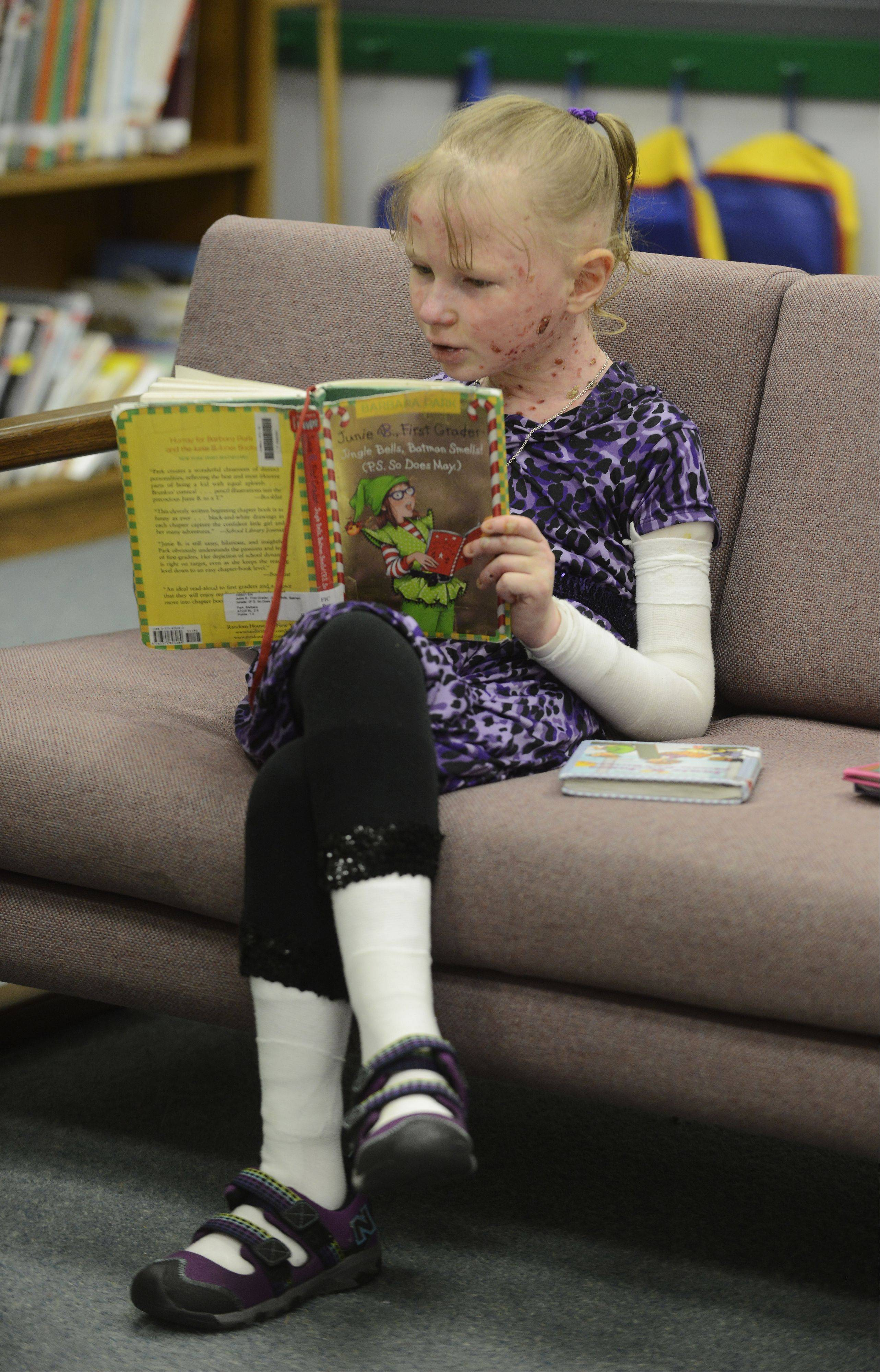 An avid reader, 2nd-grader Caroline Provost starts a book by herself while waiting for friends at Kimball Hill School in Rolling Meadows.