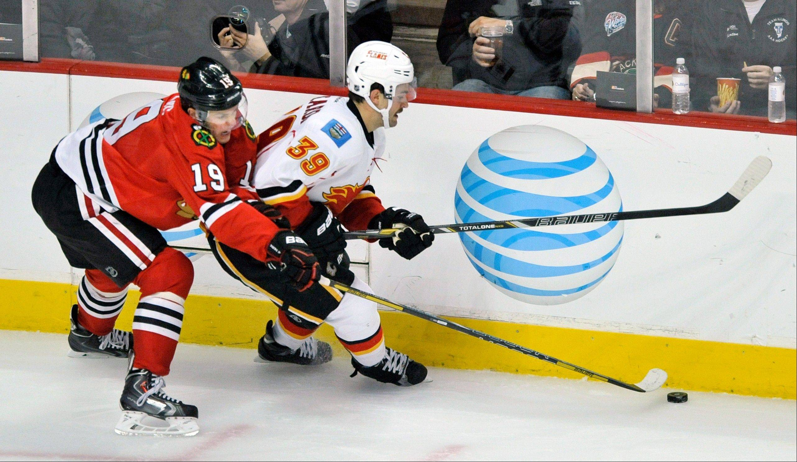 Blackhawks captain Jonathan Toews battles Calgary Flames skater T.J. Galiardi for the puck during the second period of an NHL hockey game in Chicago, Sunday, Nov. 3, 2013. Calgary won 3-2 in overtime.