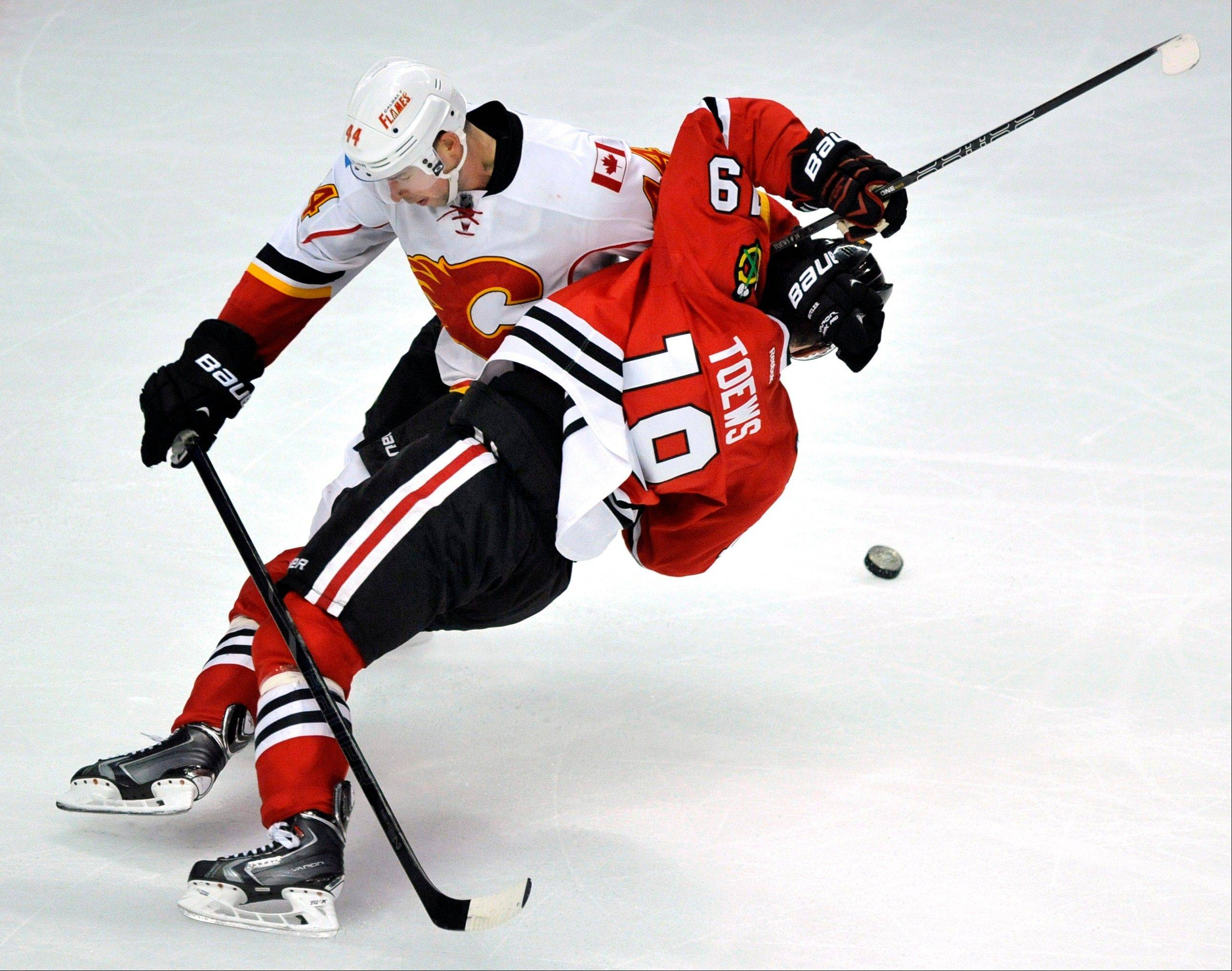 Blackhawks captain Jonathan Toews, right, battles Calgary Flames skater Chris Butler for the puck during the third period of an NHL hockey game in Chicago, Sunday, Nov. 3, 2013. Calgary won 3-2 in overtime.