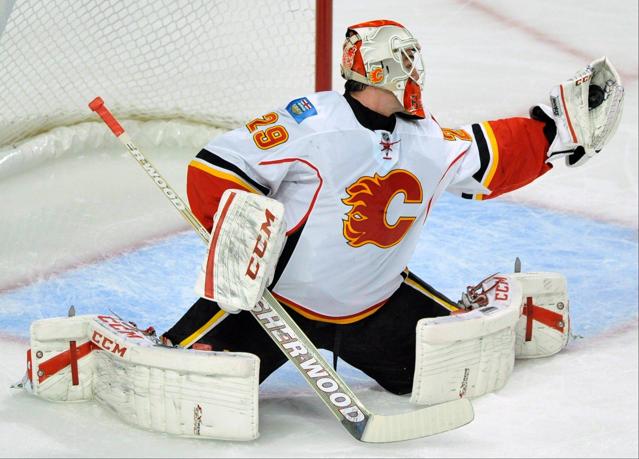 Calgary Flames goalie Reto Berra of Switzerland, makes a save during the first period of an NHL hockey game against the Chicago Blackhawks in Chicago, Sunday, Nov. 3, 2013.