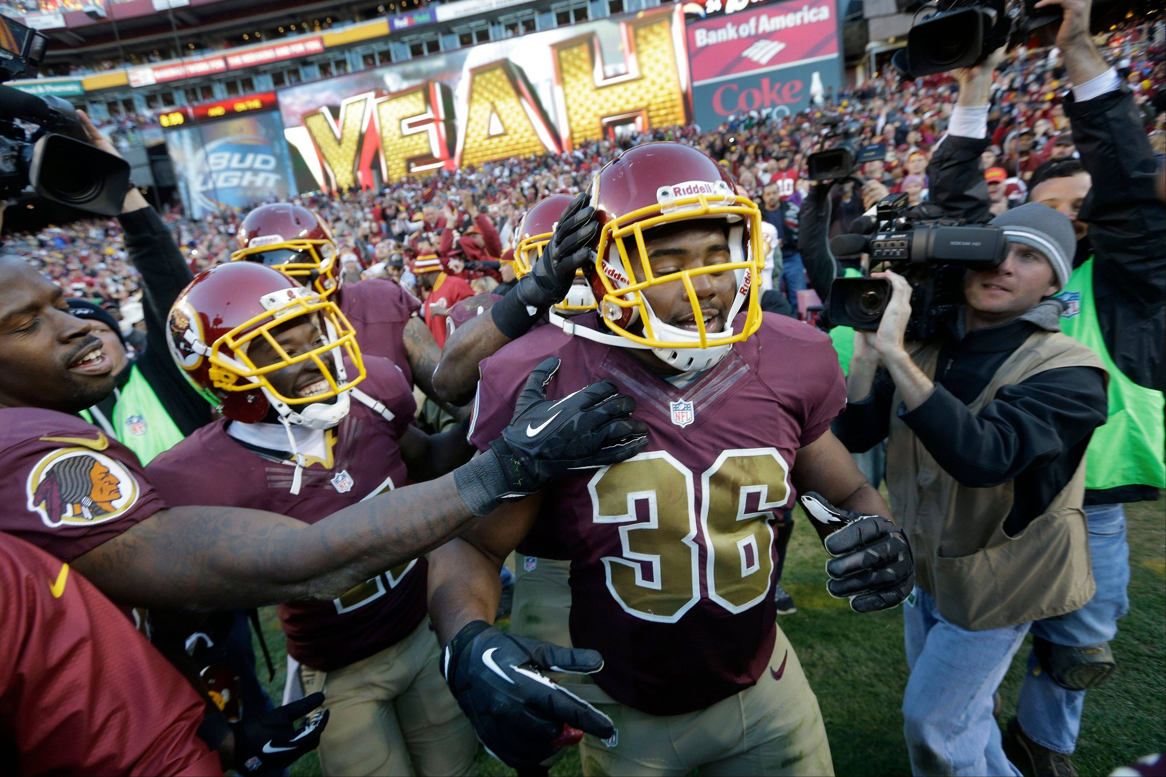 Washington fullback Darrel Young is congratulated by his teammates after scoring the winning touchdown in overtime against the San Diego Chargers in Landover, Md., Sunday, Nov. 3, 2013. Washington defeated San Diego 30-24.