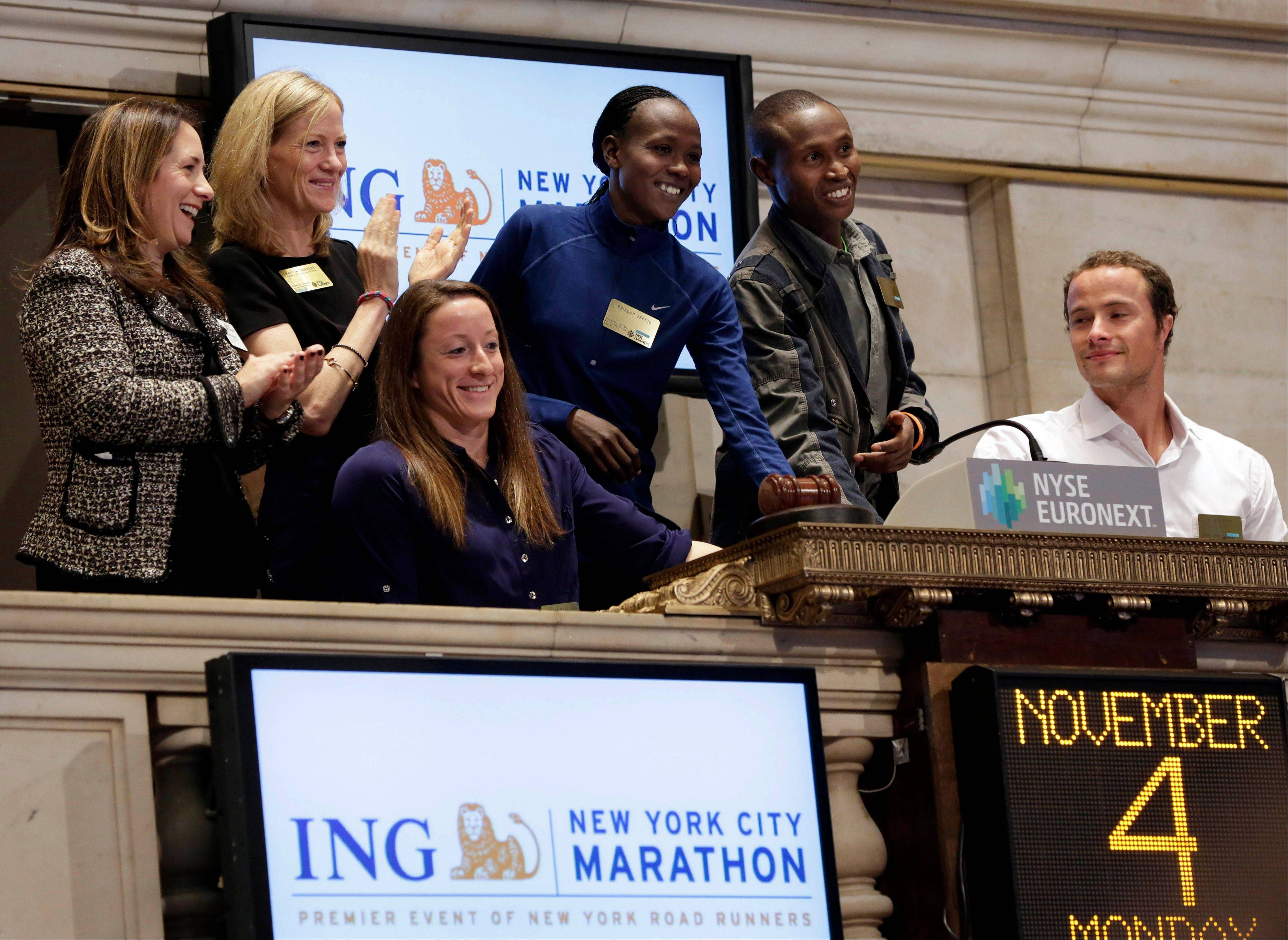 New York City marathon winners Geoffrey Mutai, fourth left, and Priscah Jeptoo, second from right, of Kenya, with wheelchair winners Tatyana McFadden, from Baltimore, Md., and Marcel Hug, right, of Switzerland, are applauded as they ring the New York Stock Exchange opening bell Monday. U.S. stocks rose, as Exxon Mobil Corp. and U.S. Steel Corp. led a commodity rally.